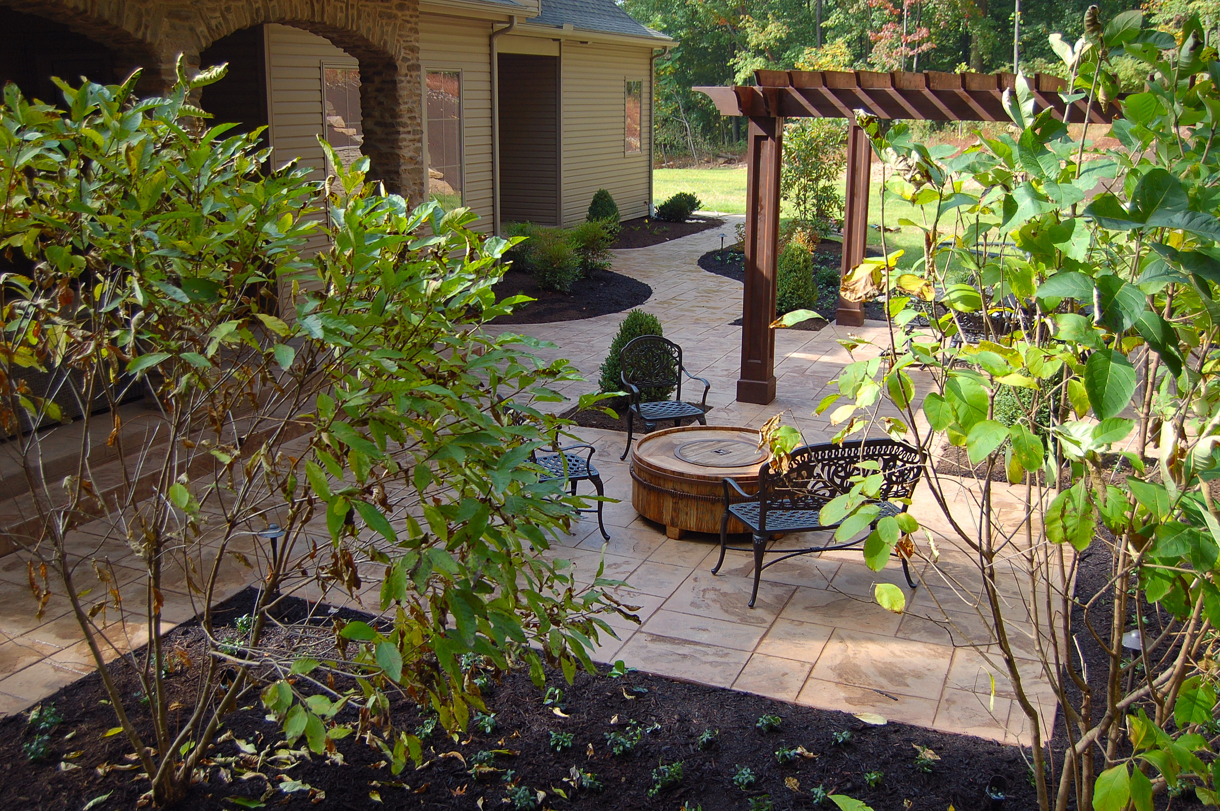Outdoor seating area with pergola and brick archway