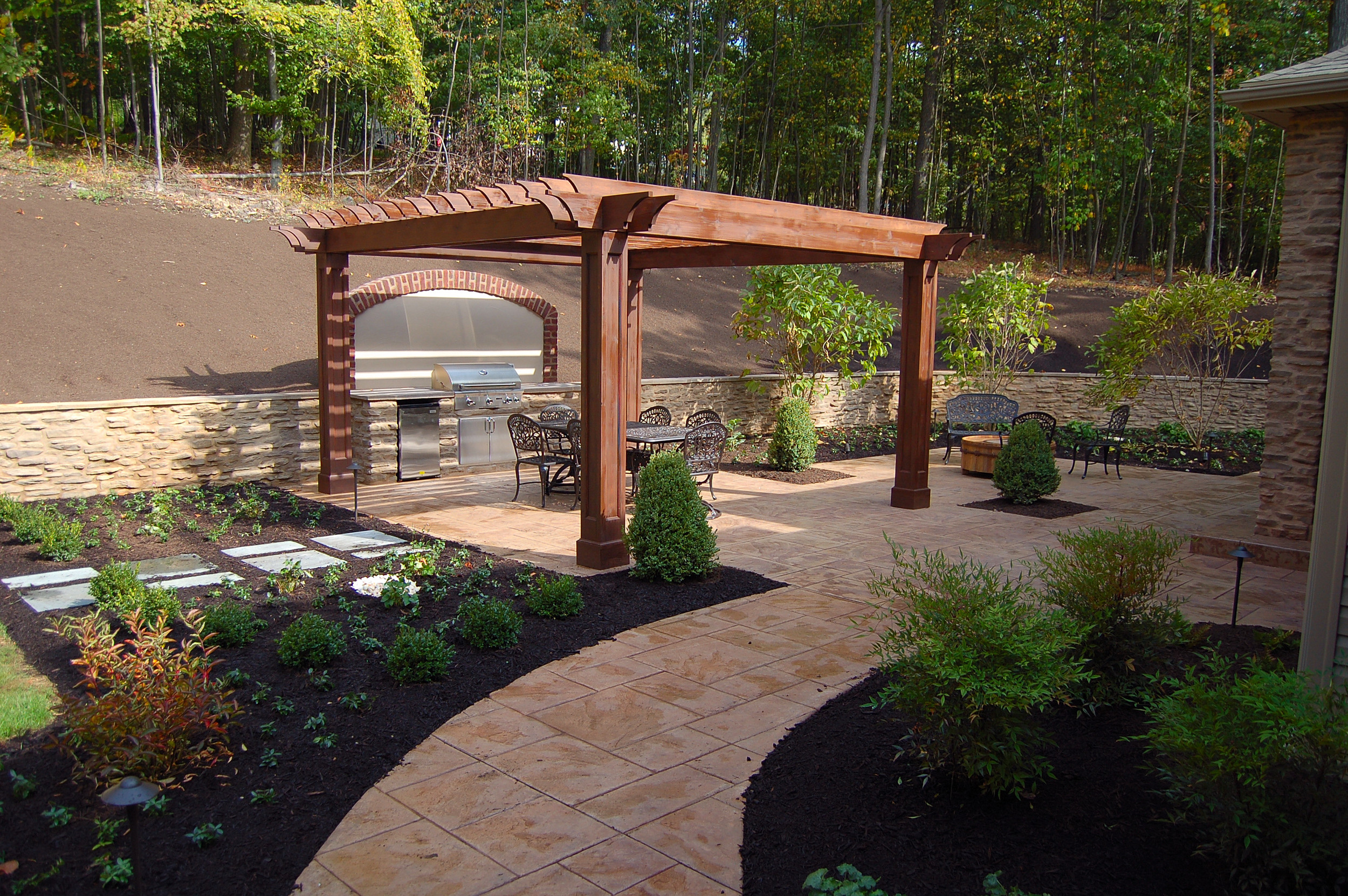 Traditional garden in Harrisburg Pa. with a pergola, outdoor kitchen, stone walls and an outdoor fireplace.