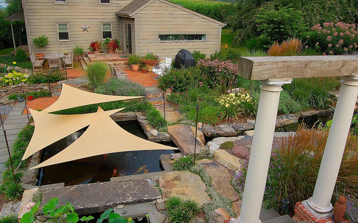 A waterproof woven shade sail covers the koi pond