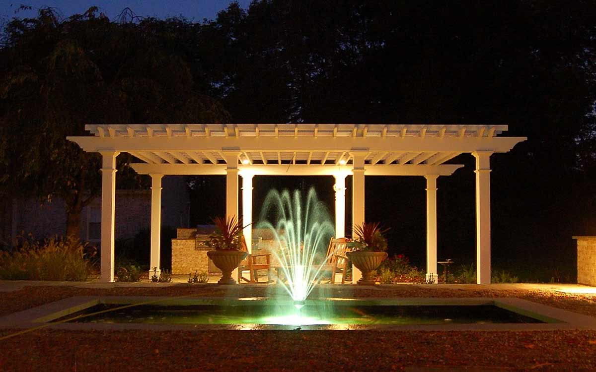 Fountain, urns and pergola at night