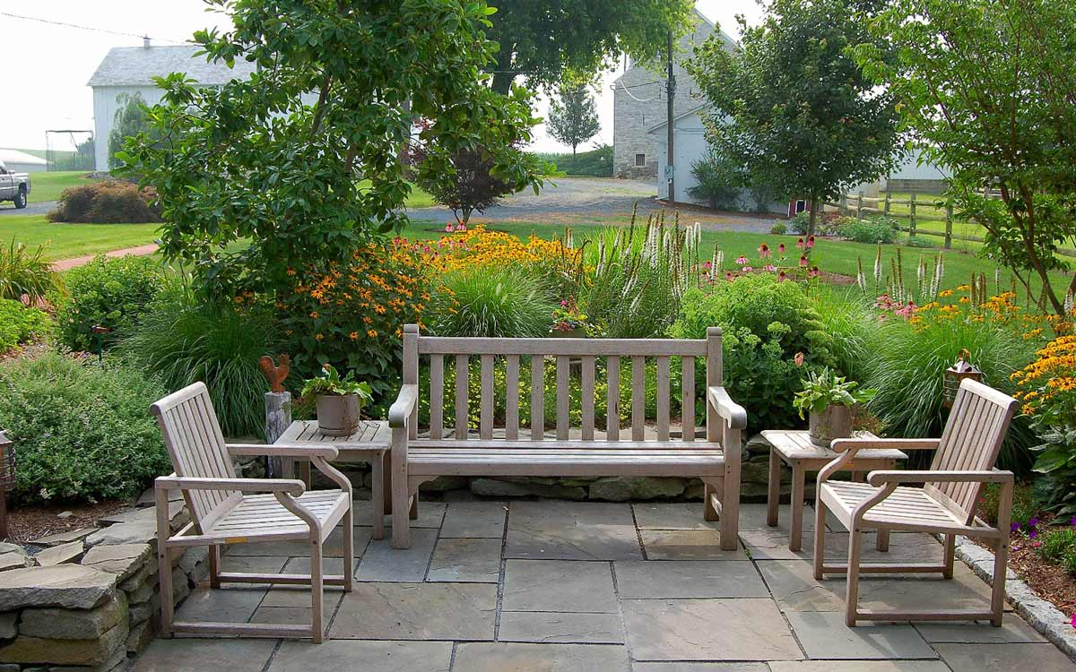 Outdoor teak furniture on fieldstone patio