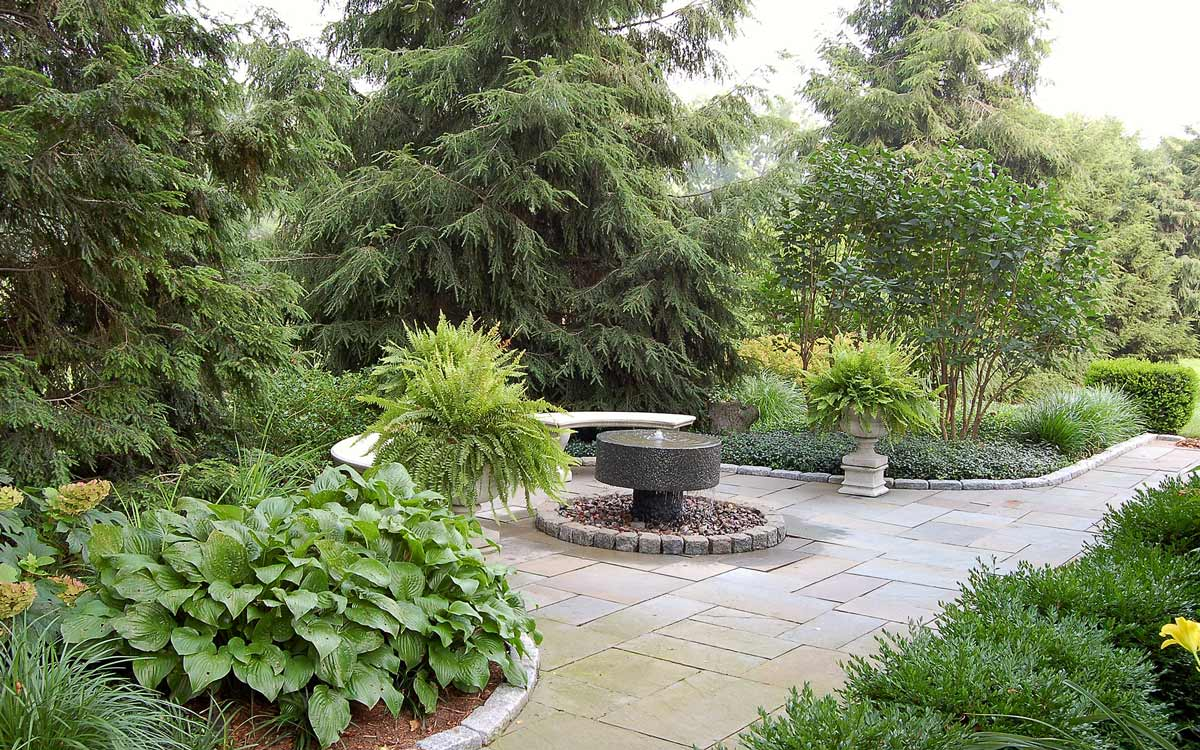 Millstone water feature with hosta