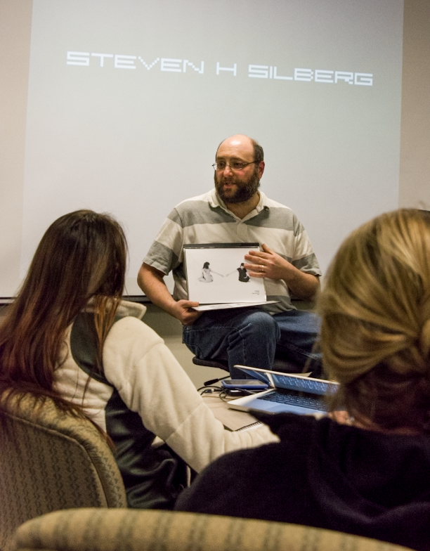 UMBC Lecturer Steven H. Silberg shows an example of one of his early-career physical portfolios to students in the 480 Photo Portfolio Development course at Stevenson University Feb. 25.