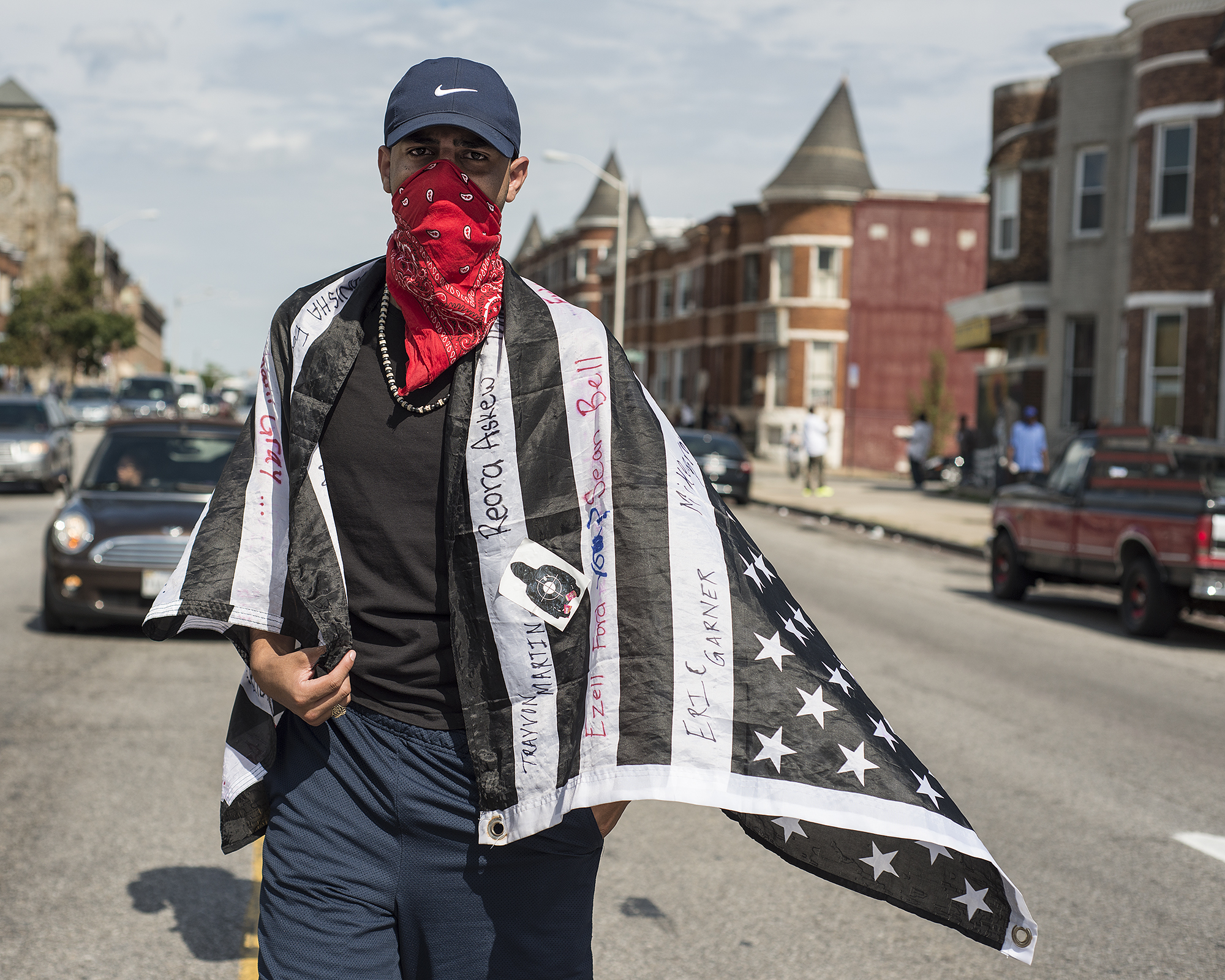 A protester walks in the march down North Avenue wearing a flag upon which is written the names of people who have faced police violence.