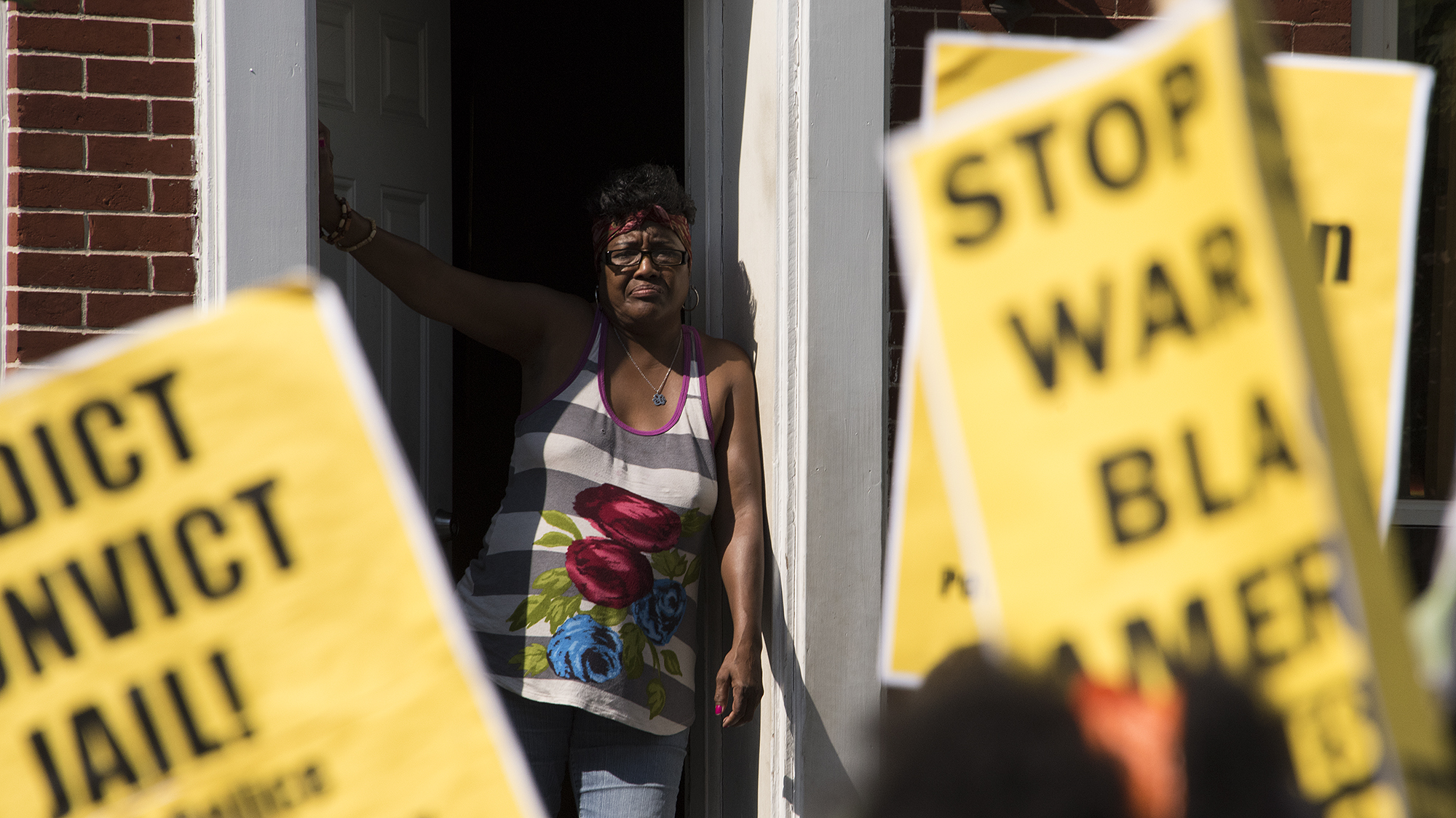 A Baltimore resident stands in her doorway to watch the march pass by.