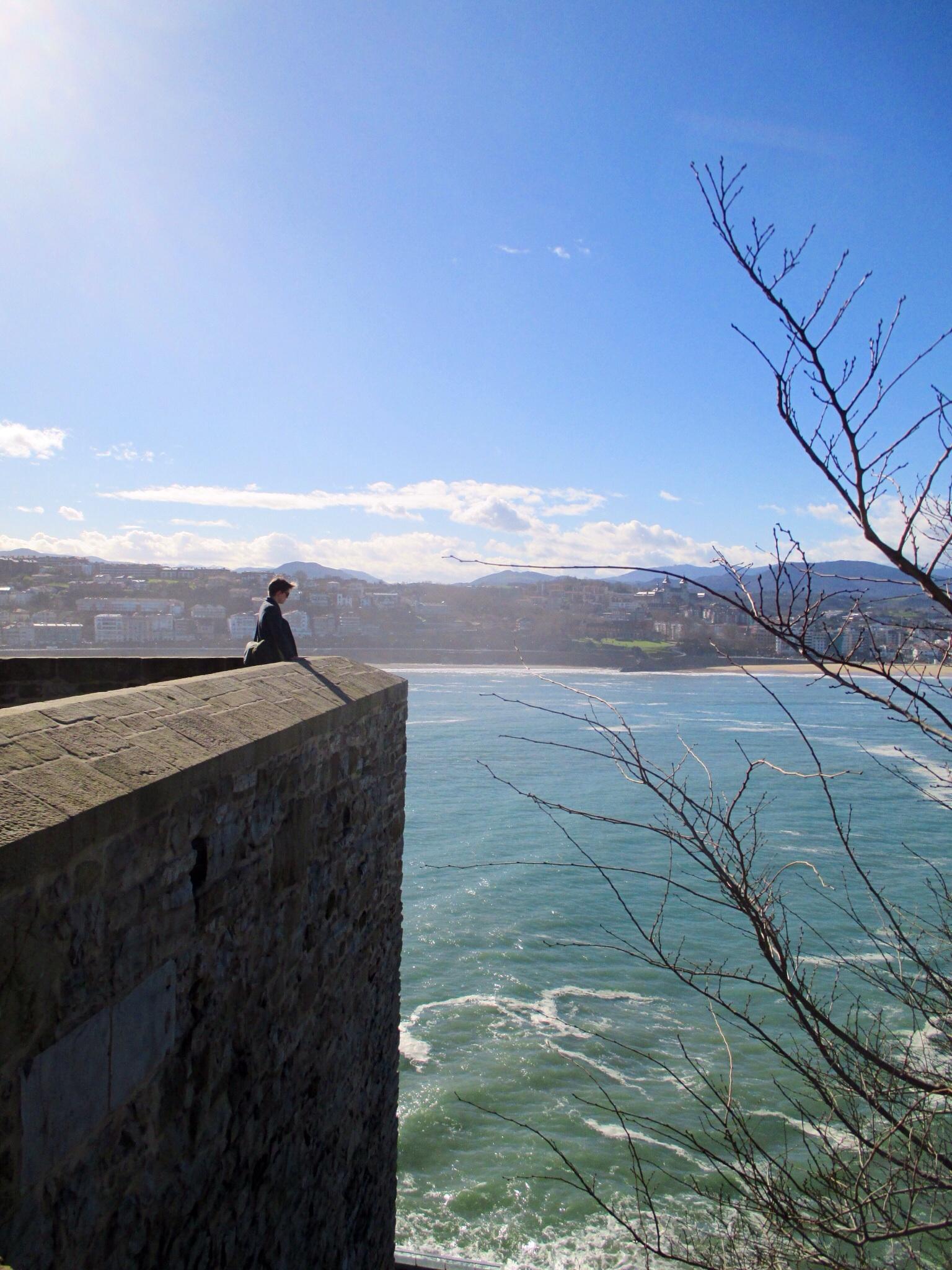 Samantha watching the waves crash onto the shoreline of San Sebastián
