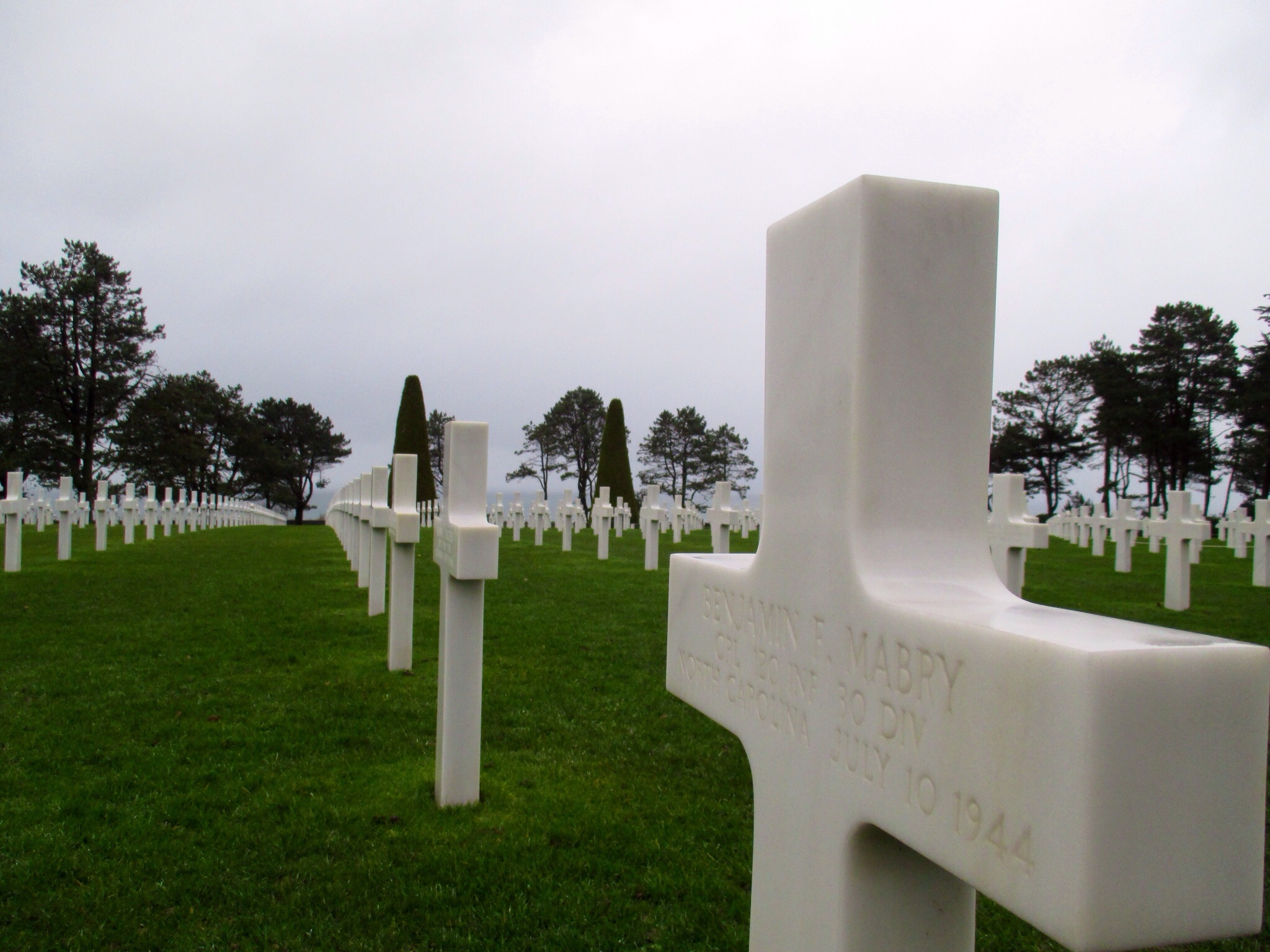 Grave of a soldier killed about a month after the landings in perfect symmetry with his fellow soldiers at the American Cemetary