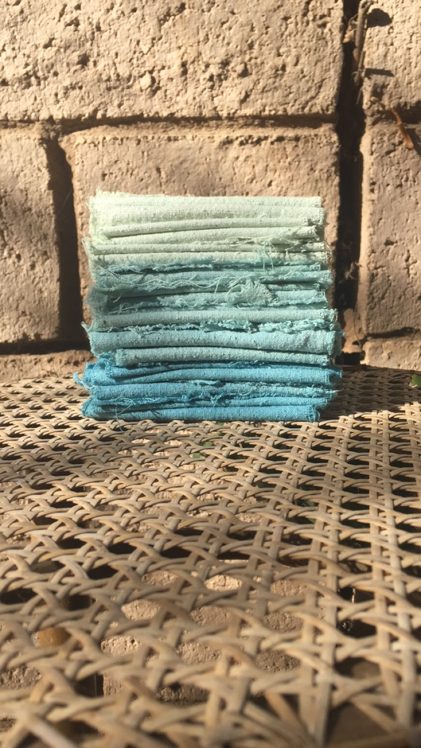 fresh indigo dyed raw silk- from bottom to top a range of blues and greens produced as the dye bath exhausts