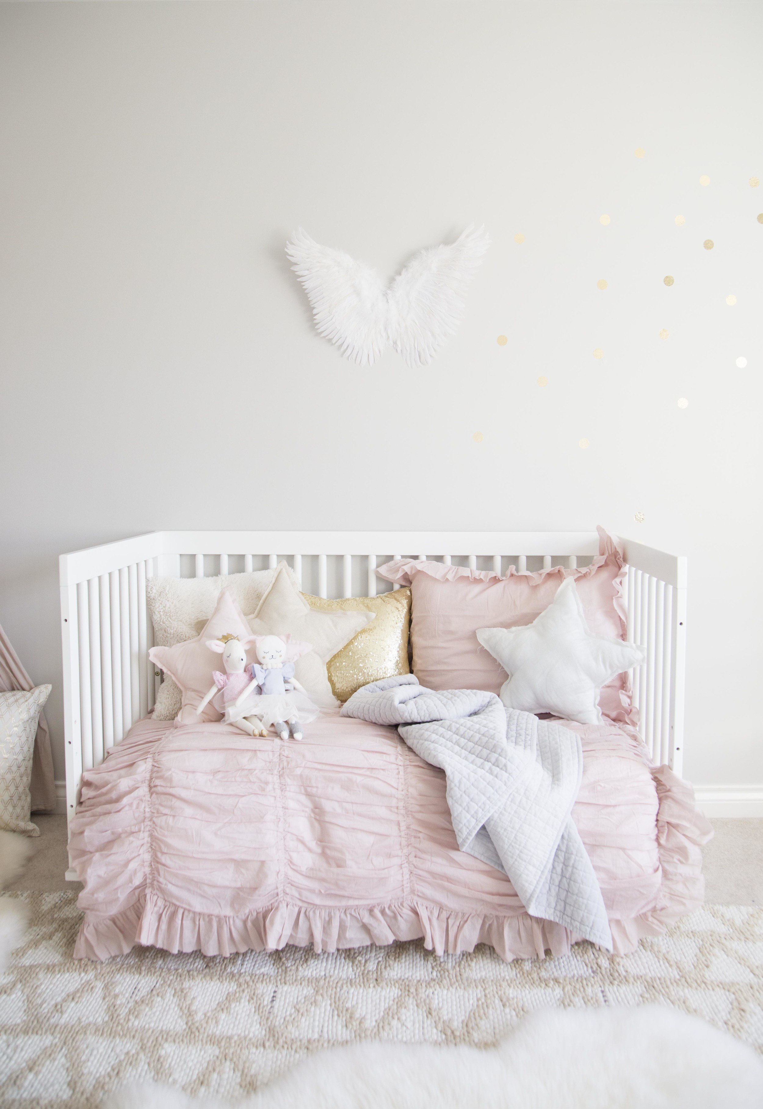 soft pink bedding on girl daybed with star pillows and angel wings on wall behind
