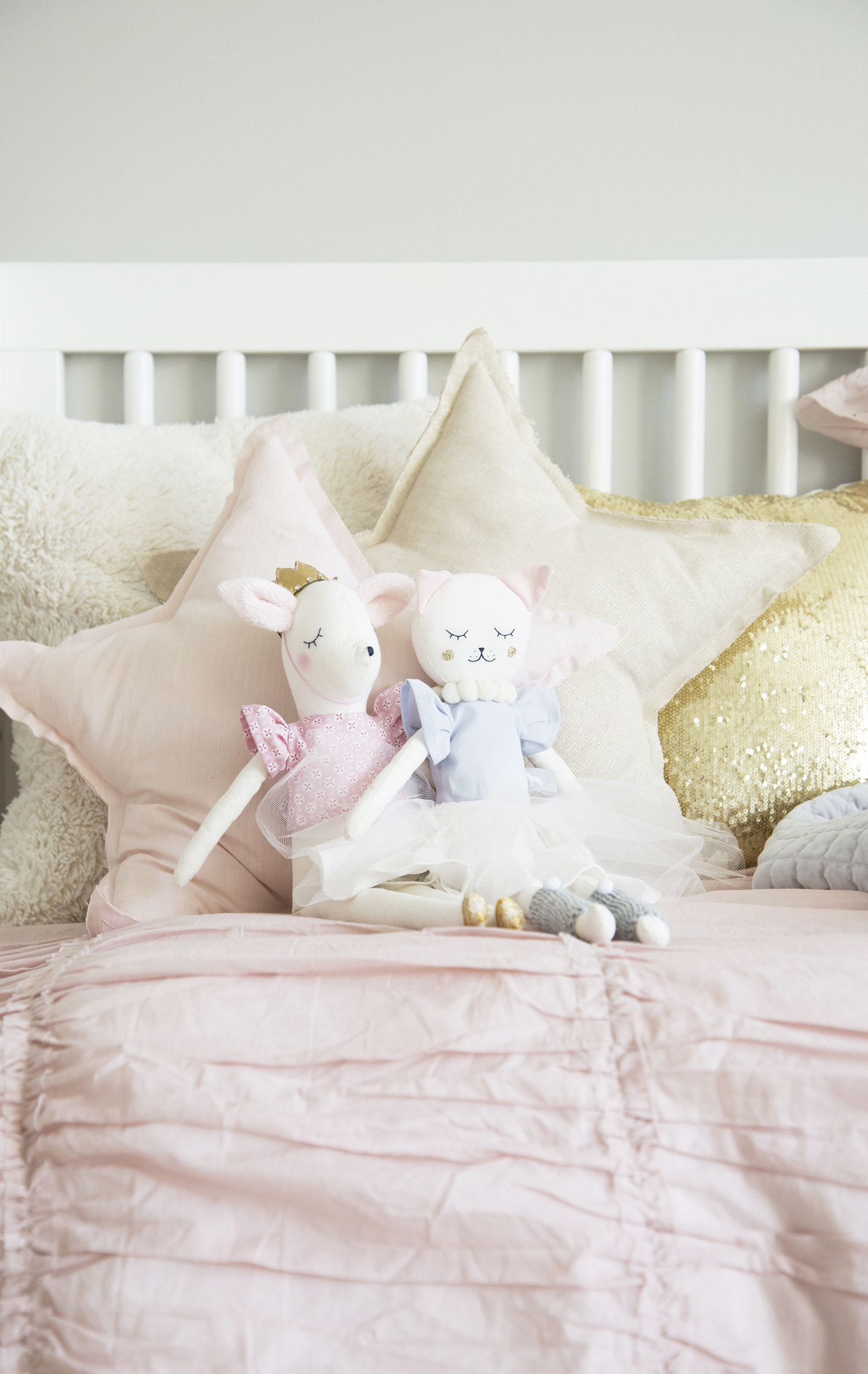deer and kitty stuffed animals on daybed