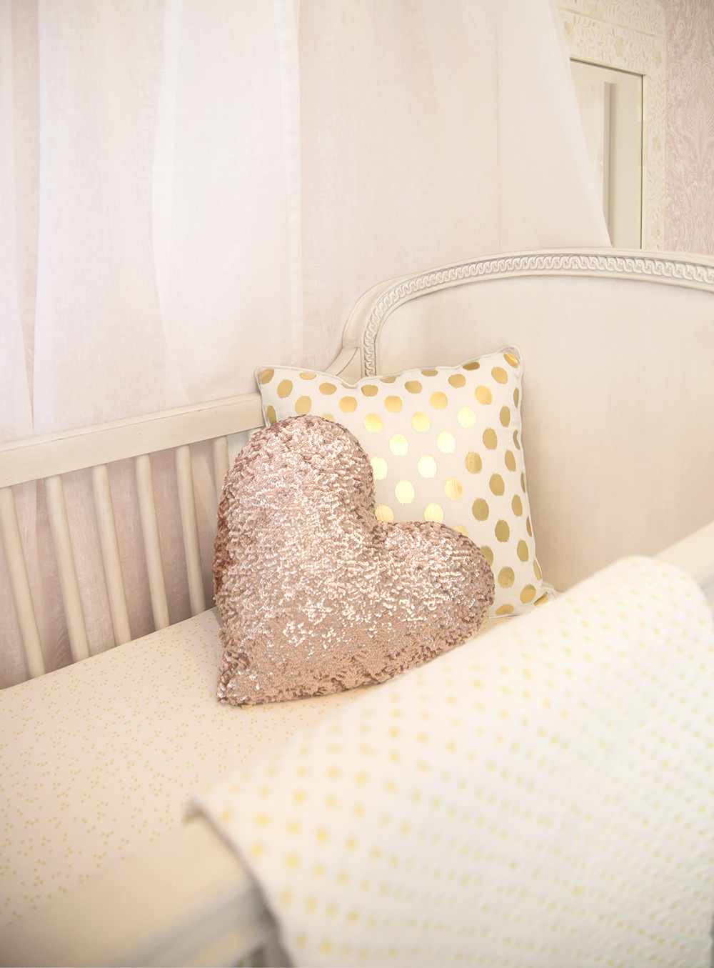 Heart and gold pillows in crib