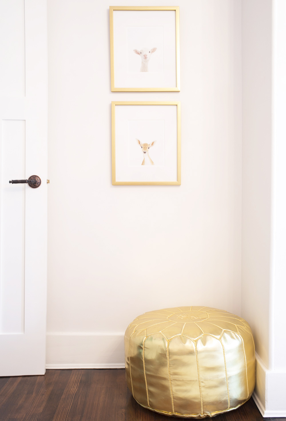 Animal print shop art hangs over gold ottoman