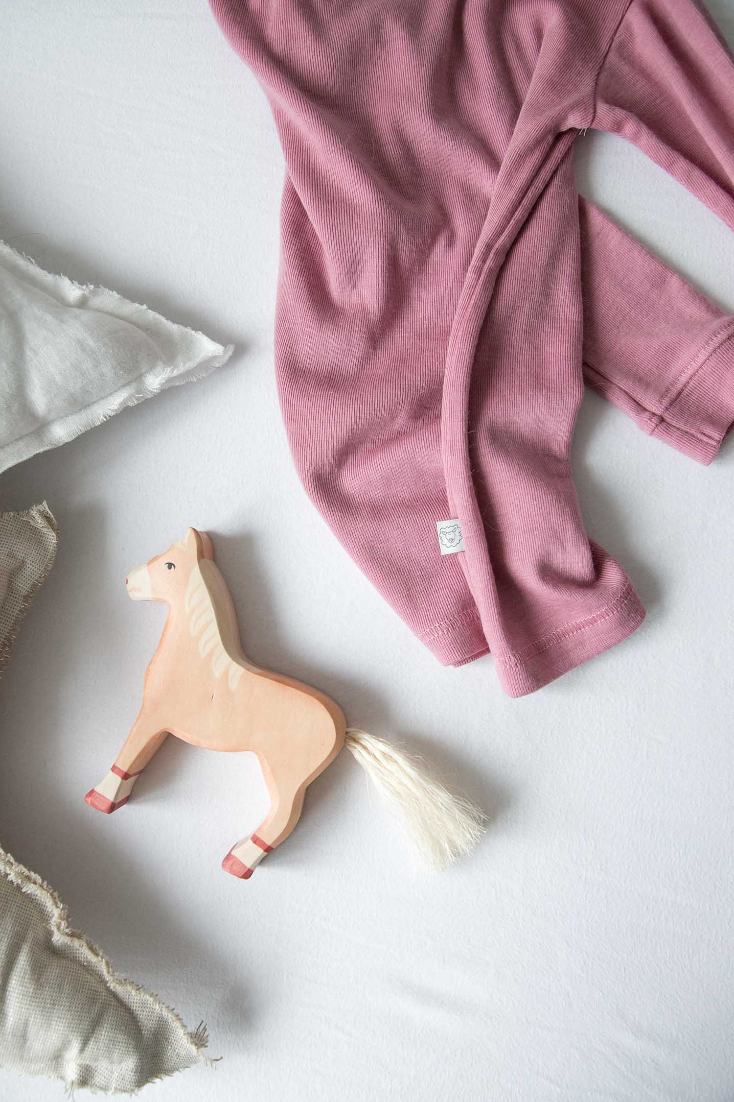 wooden horse with detail of pink merino wool pajamas