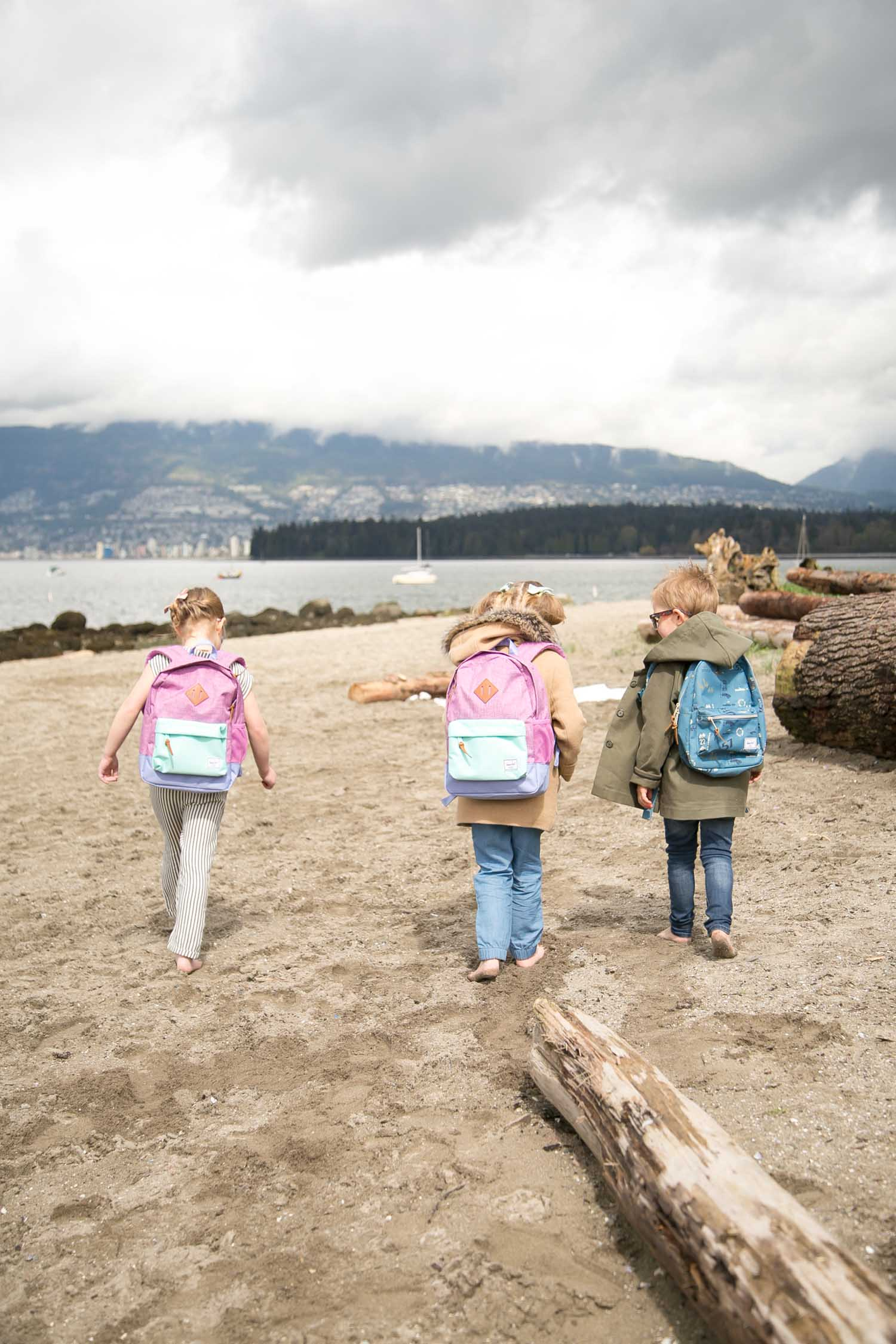 kids walking on beach with hershel backpacks