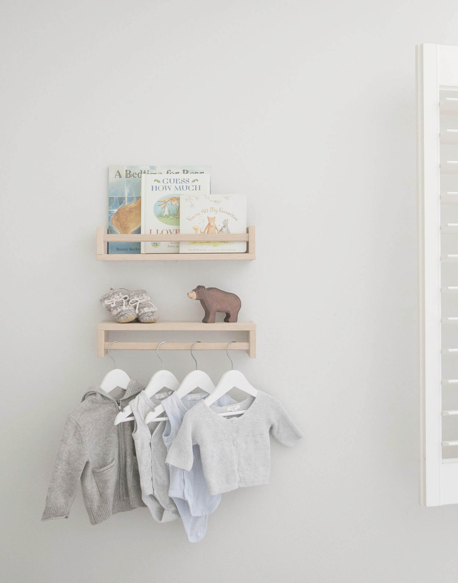 shelves with baby clothes, books and toys in kids nursery