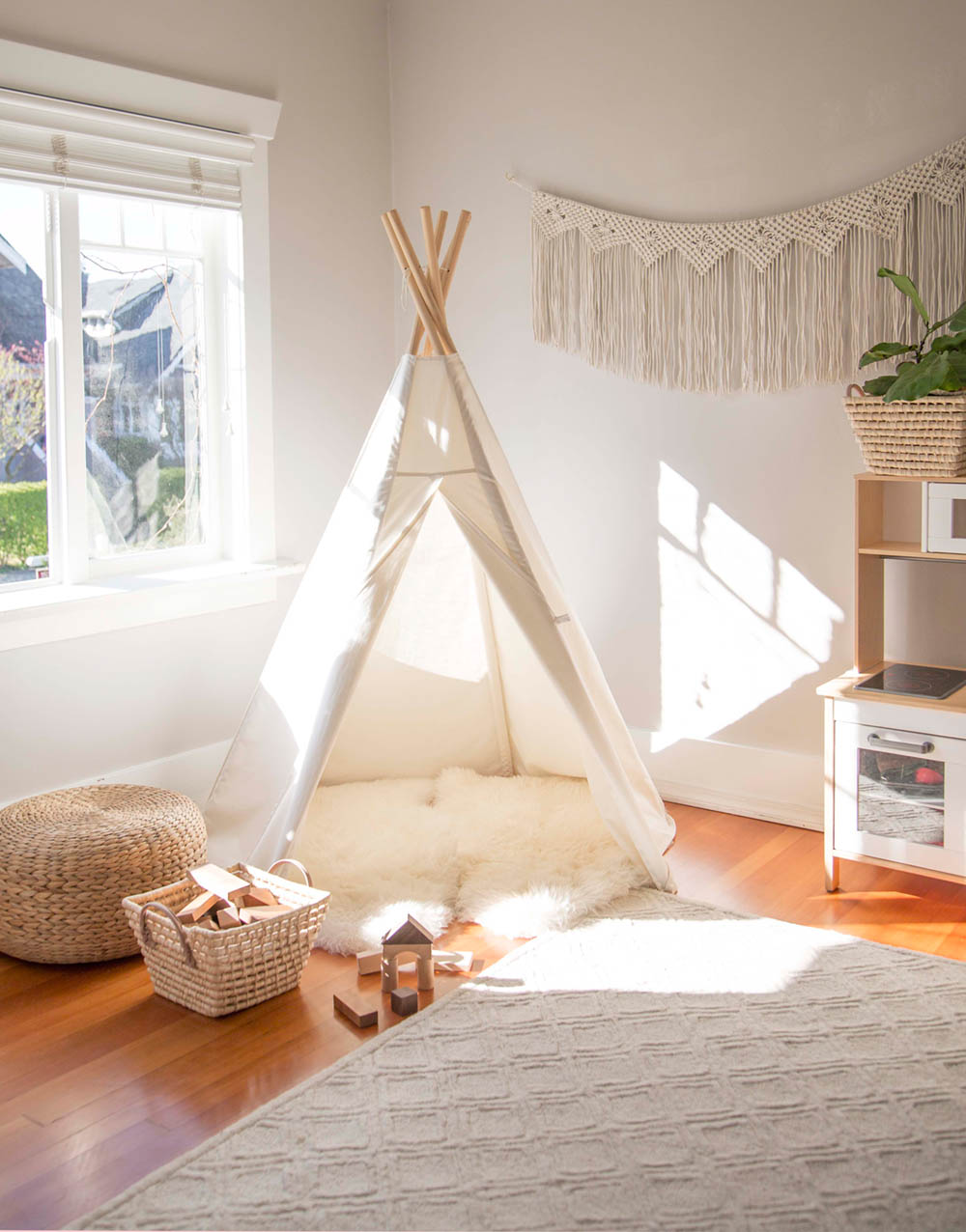 kids play teepee in neutral playroom
