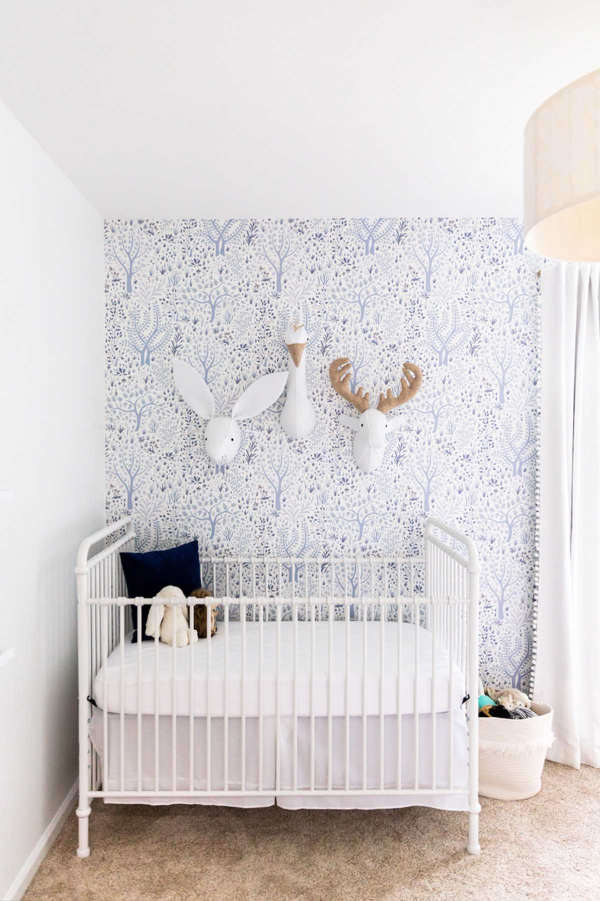 white iron crib in baby nursery with wallpaper