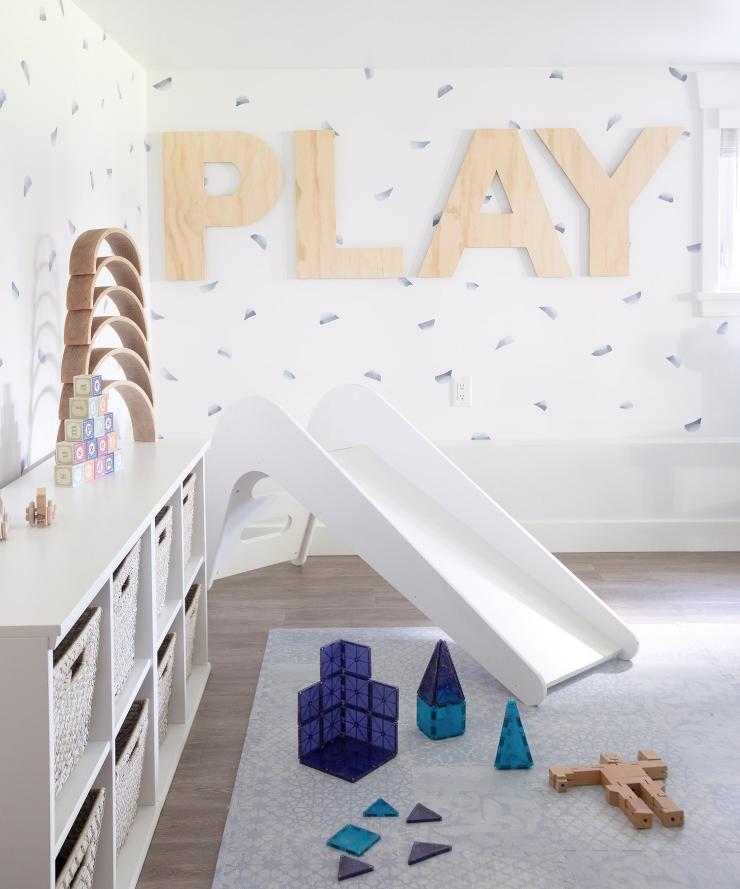 kids playroom with white slide and PLAY letters