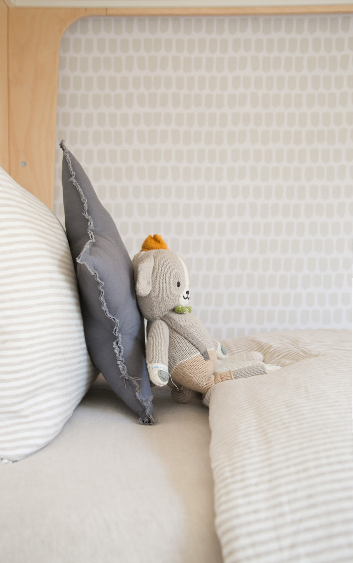 close up of the bedlinen and wallpaper with Cuddle + Kind softie