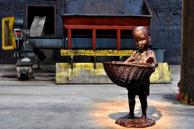 A molasses-coated boy attending Kara Walker's sugar sphinx (image:  Hrag Vartanian for Hyperallergic)
