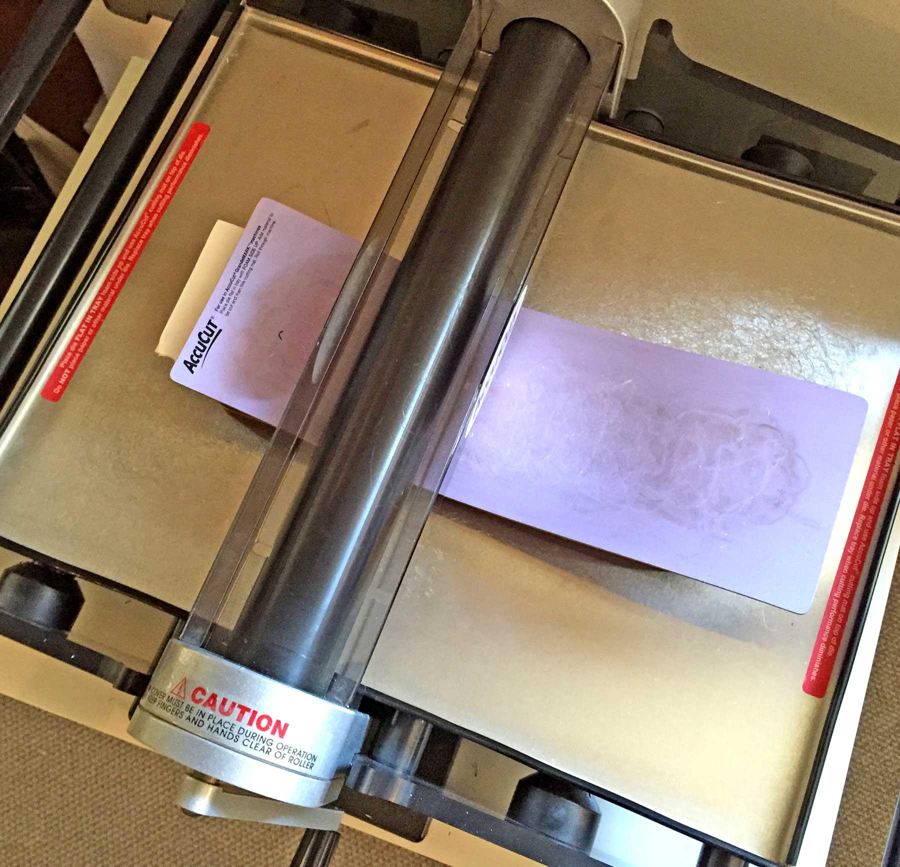 Running the die/paper/mat sandwich through the die cutter. ©2016 Kelly M. O'Brien.