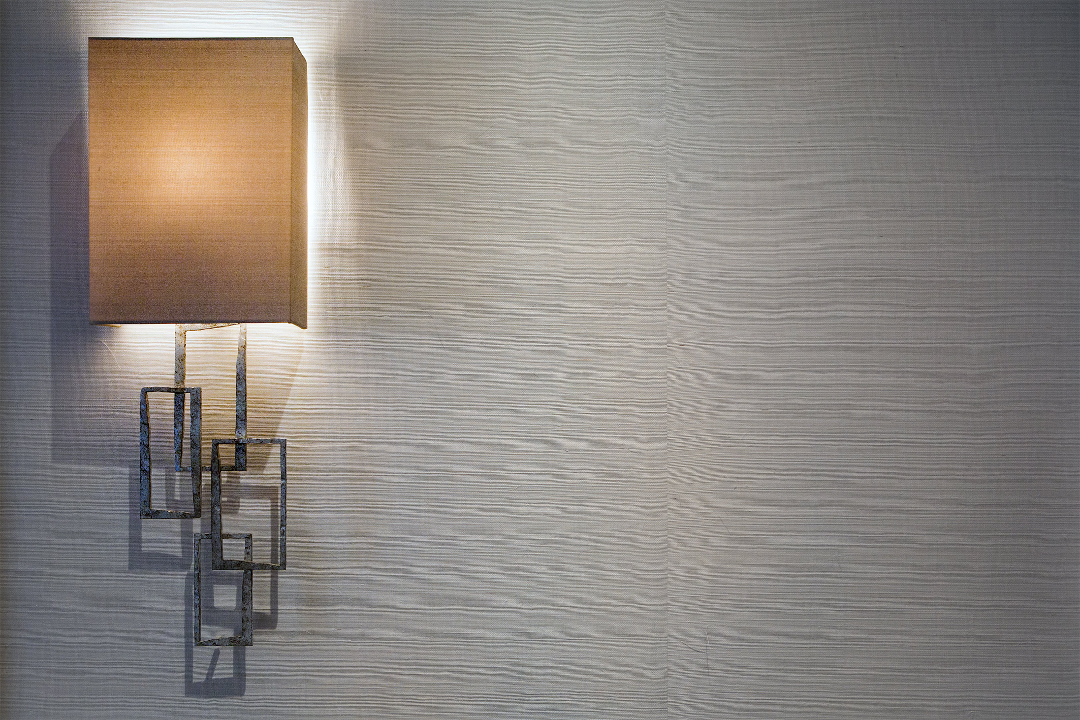 A sculptural wall light is silhouetted against a fine grasscloth wall covering