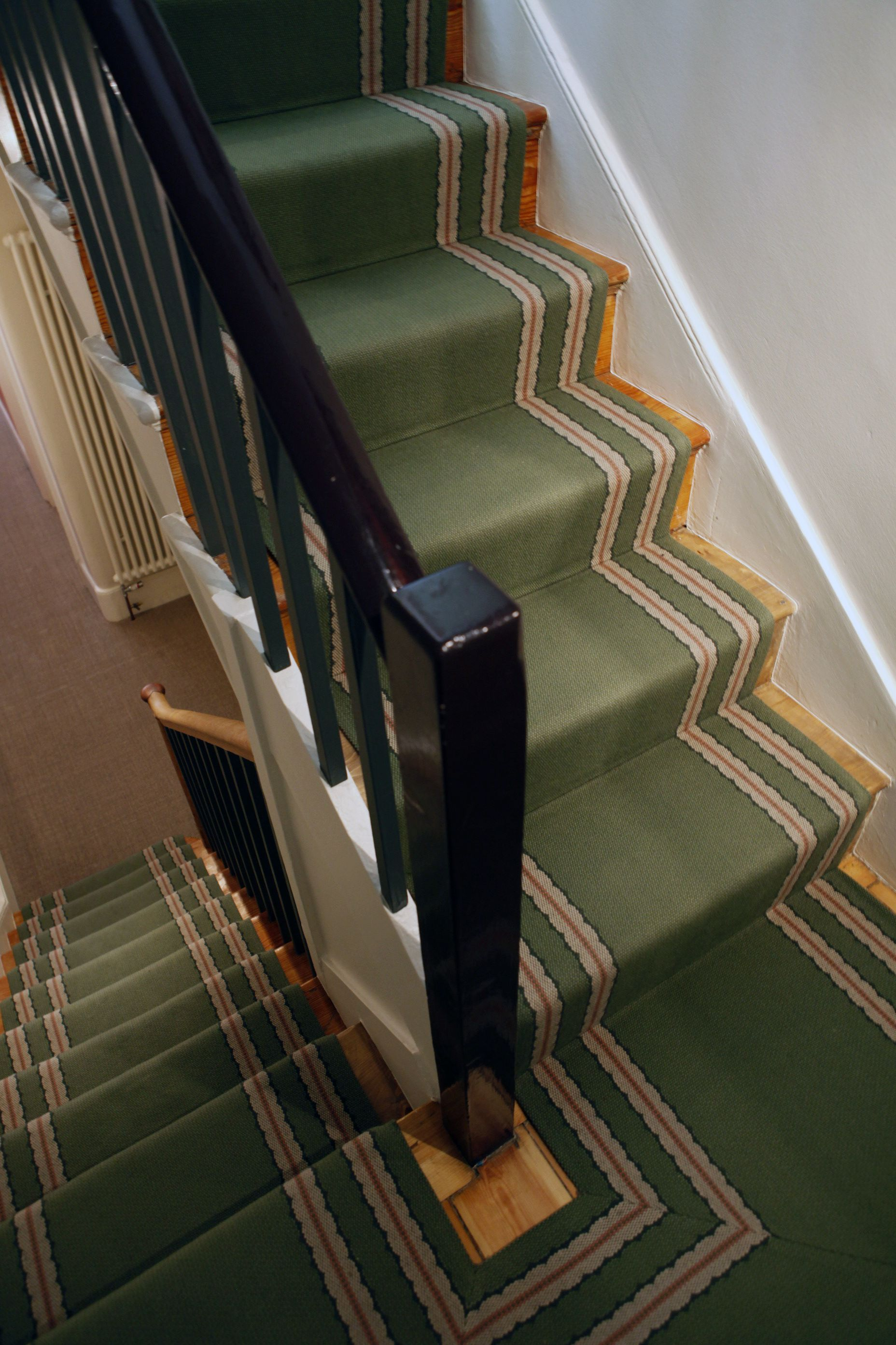 Green runner and painted spindles and banister to highlight architectural detail