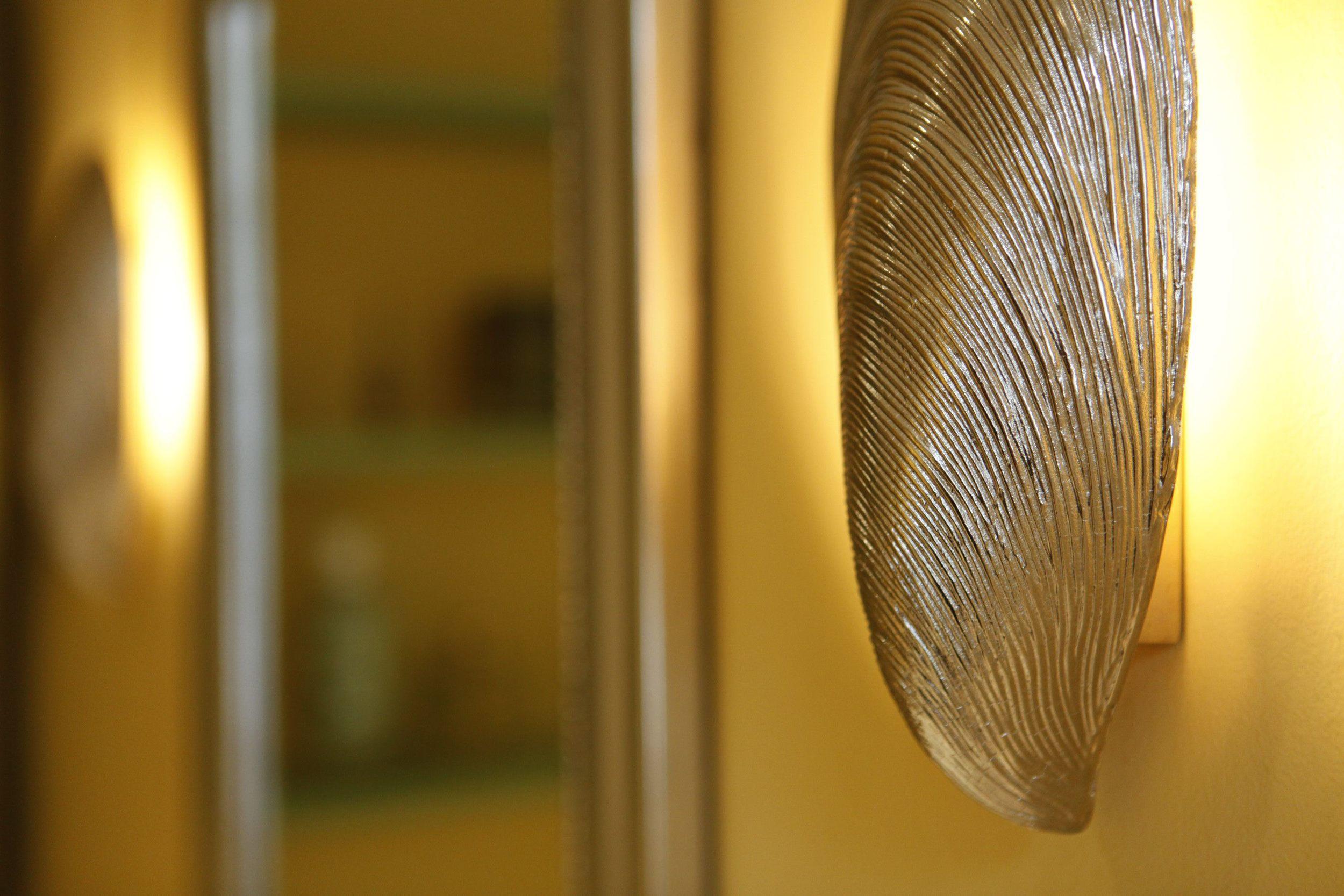Shell lights create a warm glow around a silver mirror