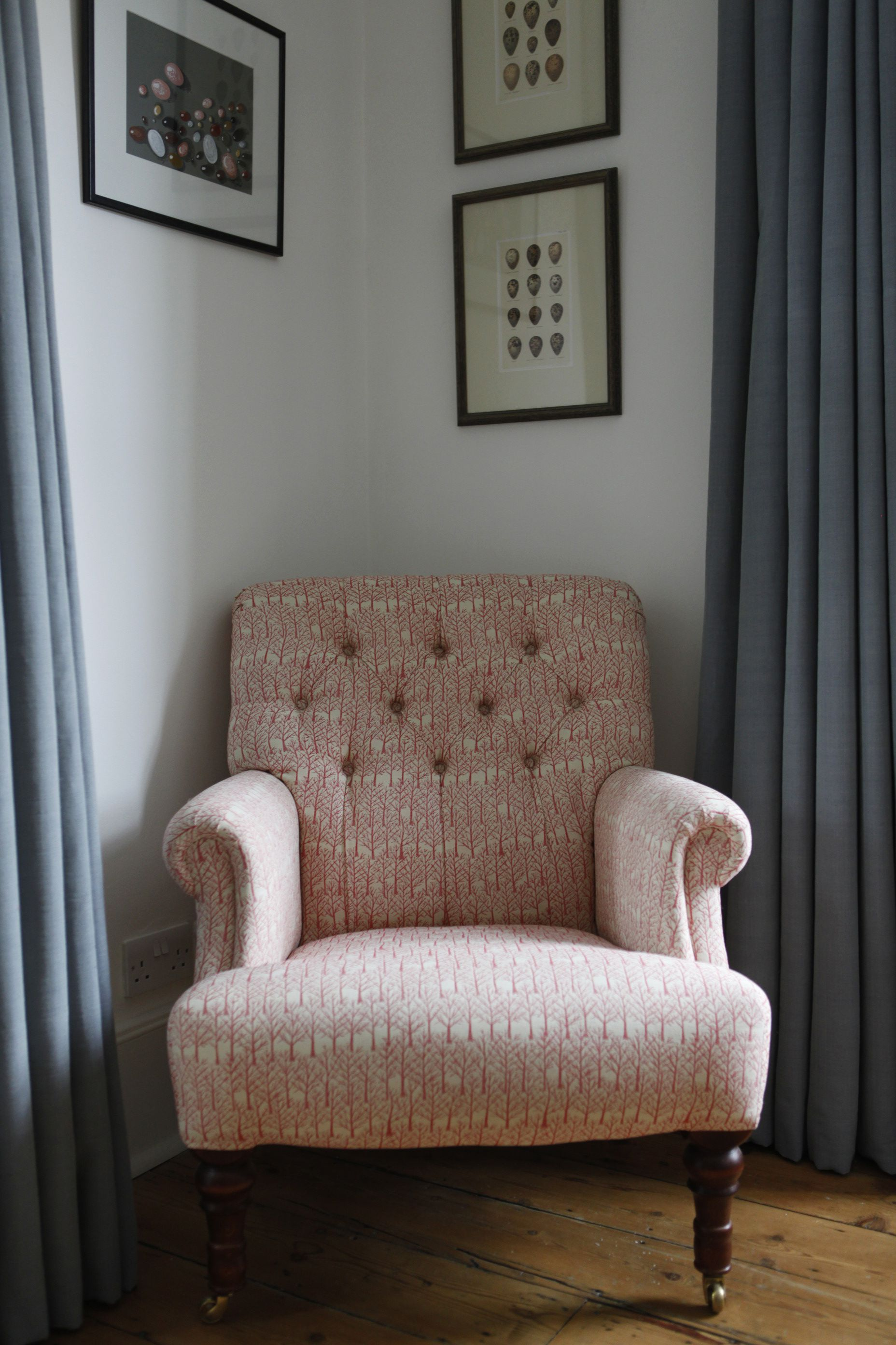Chair in a coral coloured fabric and cool blue curtains