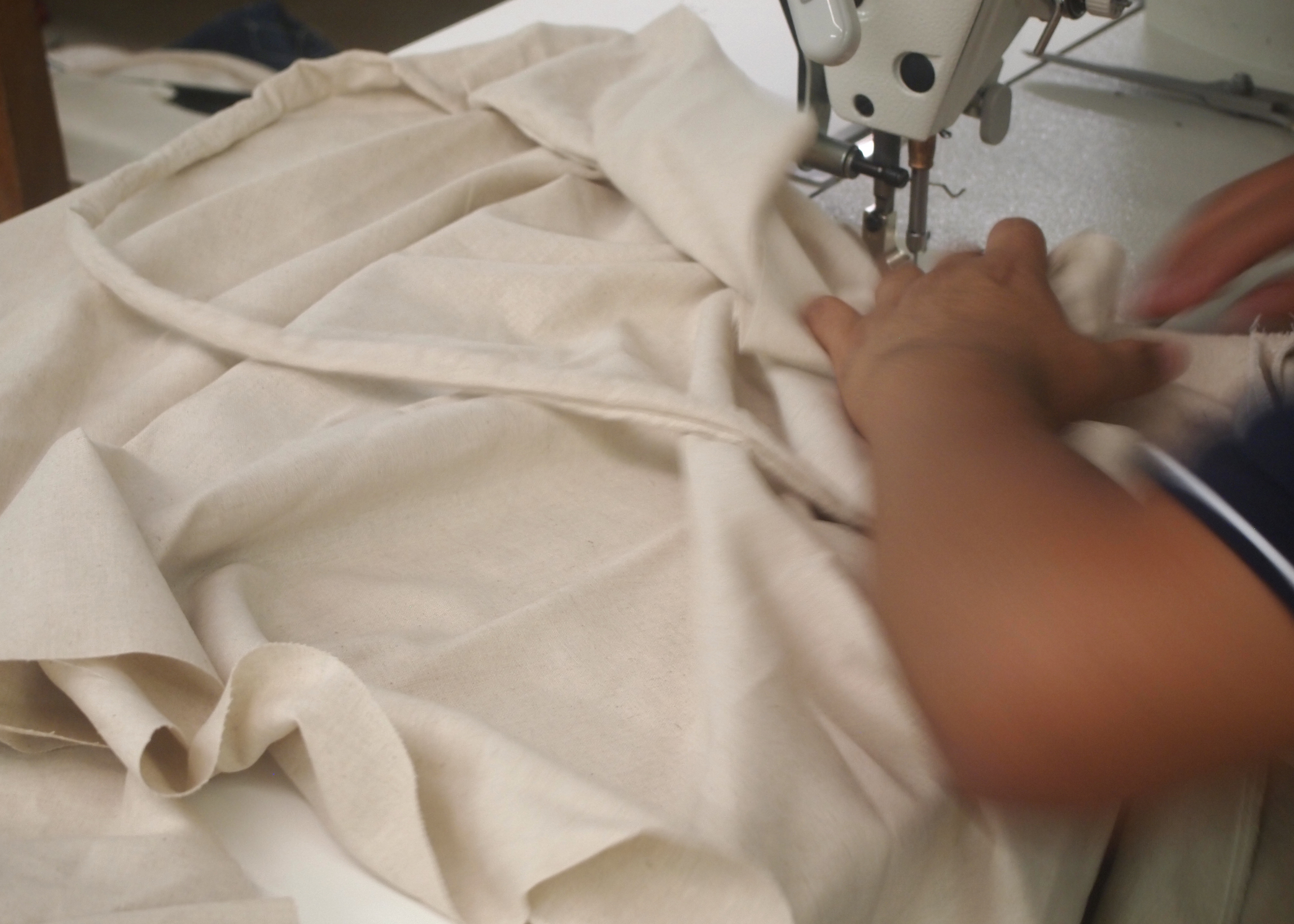 A sewer at Opportunity Threads stitching the waistband to the skirt of the Bicycle Wrap Skirt.