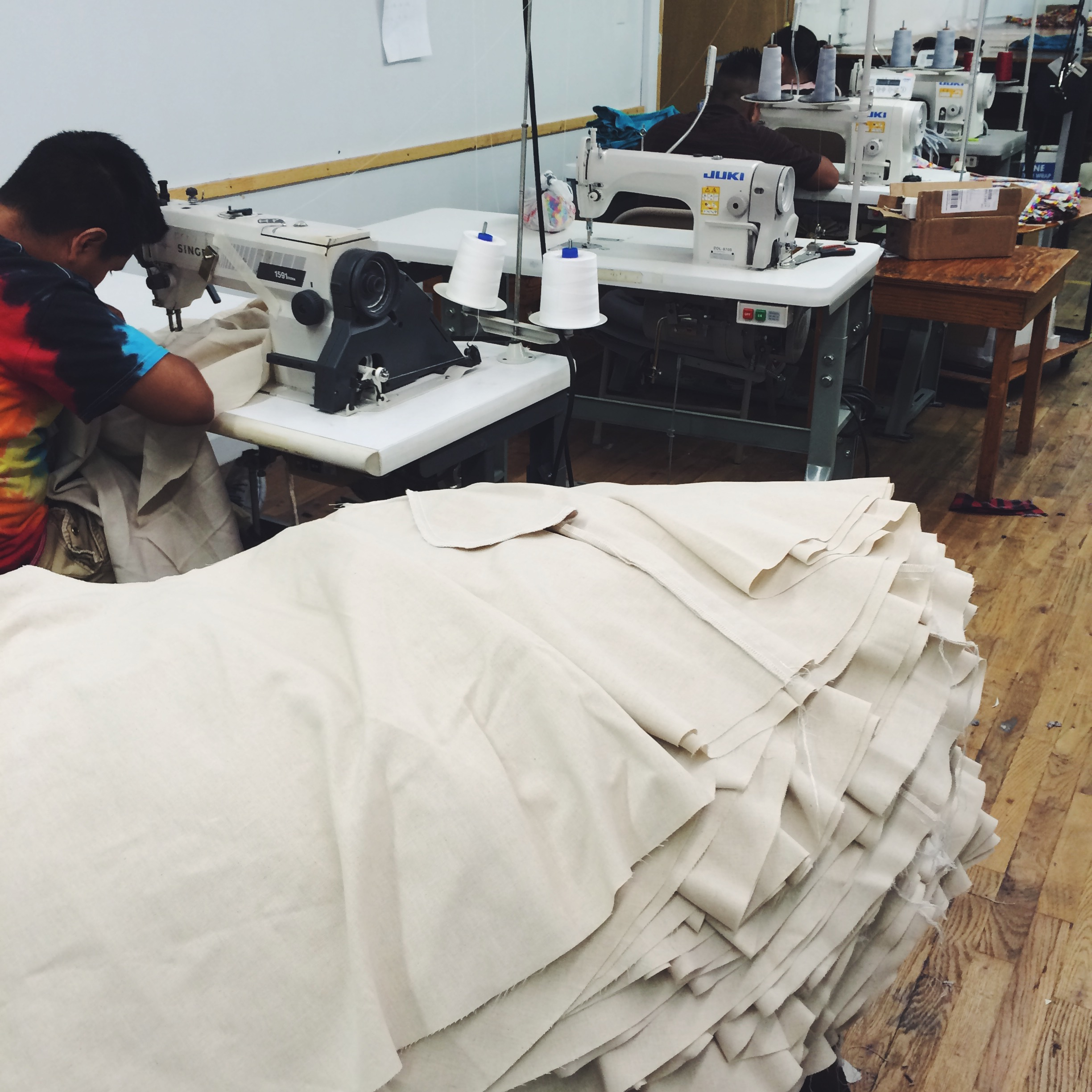 A skilled sewer stitches pockets to the skirt pieces.