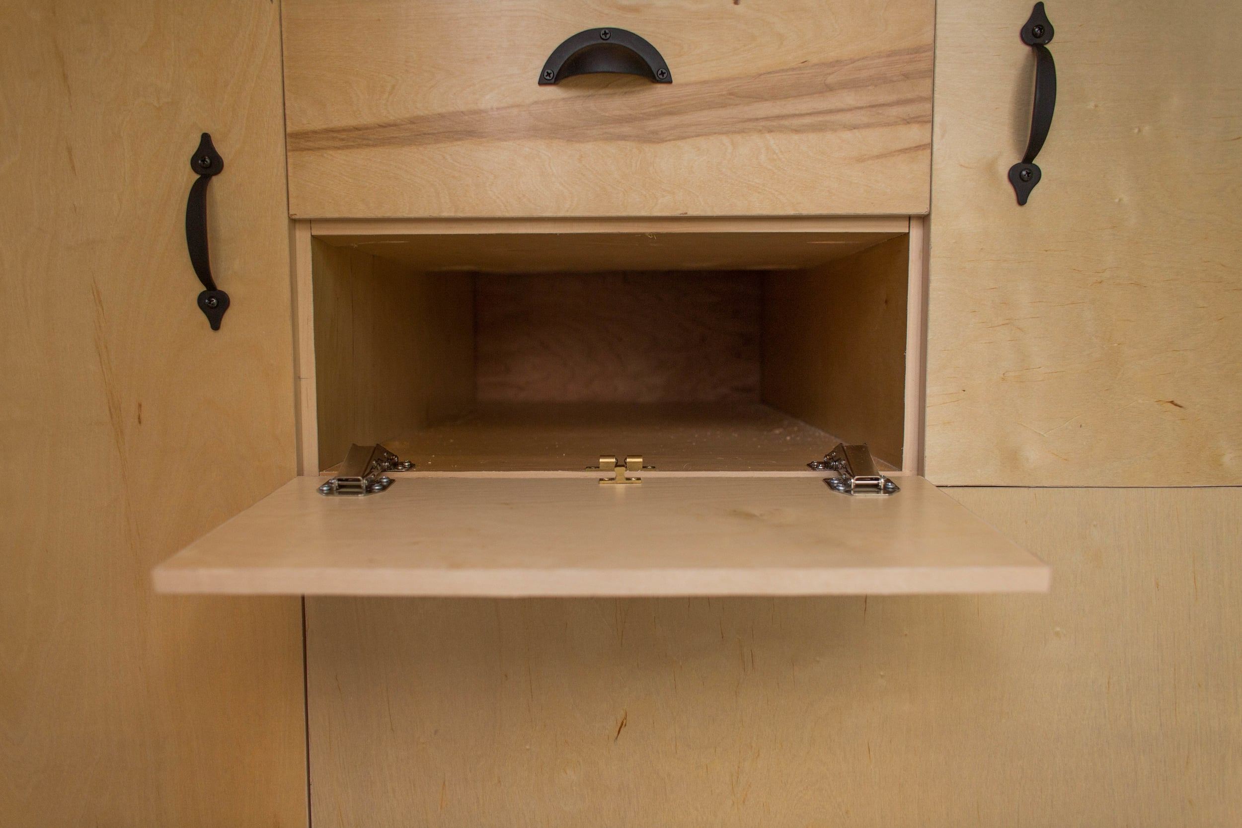 Flipdown compartment to store dishes and cookware.  Brass latch can be seen in the middle