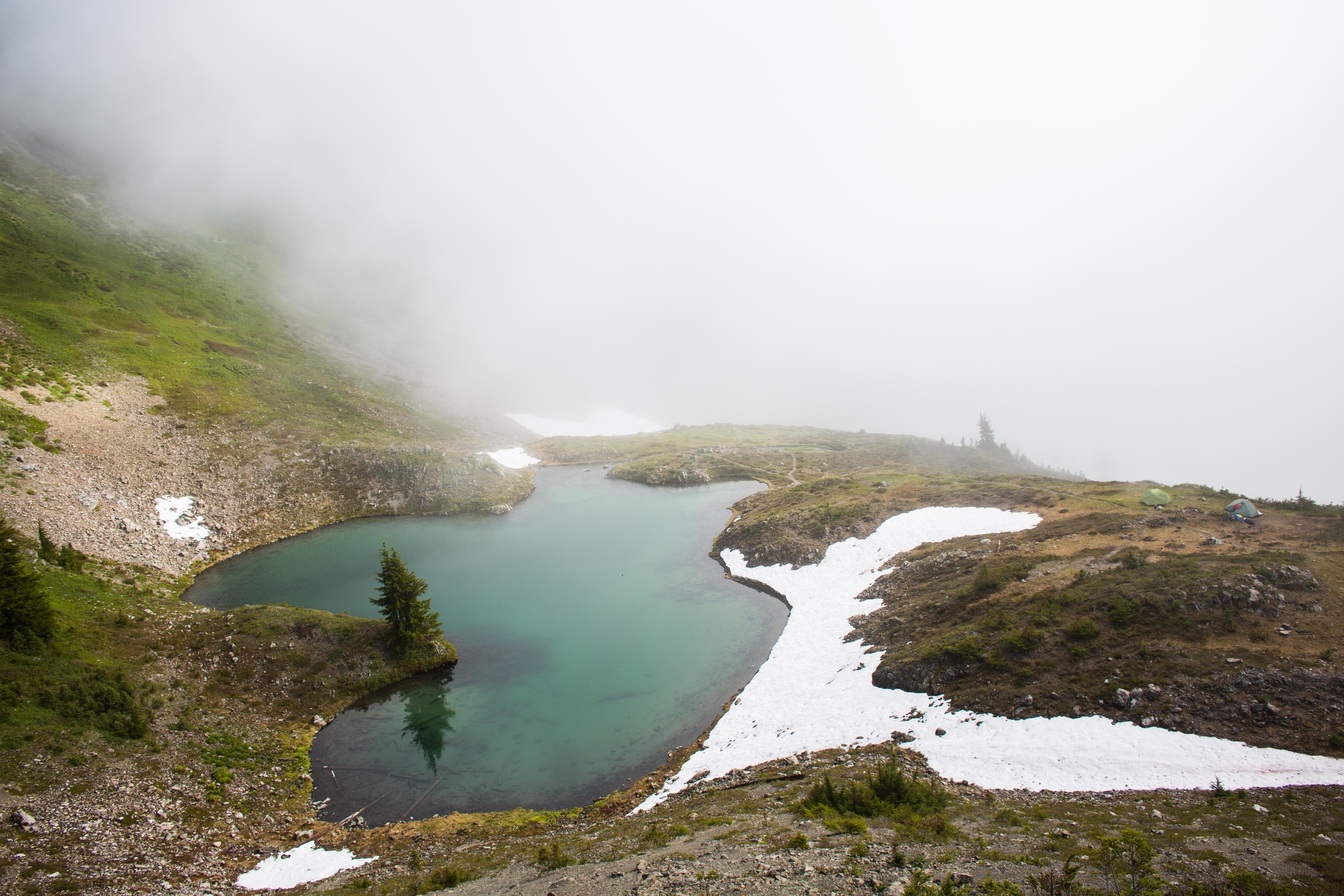 Swimming Bear Lake. Cat Basin drops steeply down beyond the fog, with mountains in the background, but they were hiding most of the time.