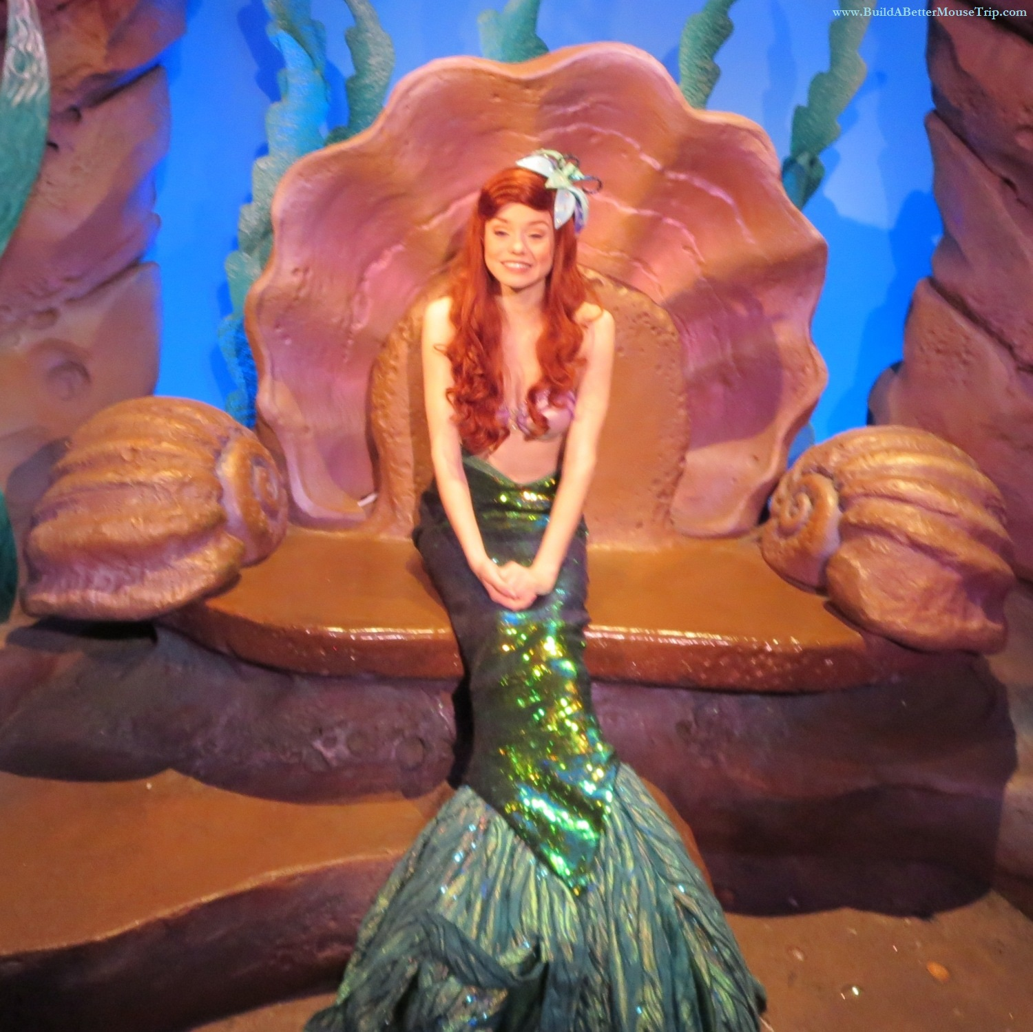 Ariel, the Little Mermaid, meets guests and poses with them for photos in her Grotto in the Magic Kingdom at Disney World.