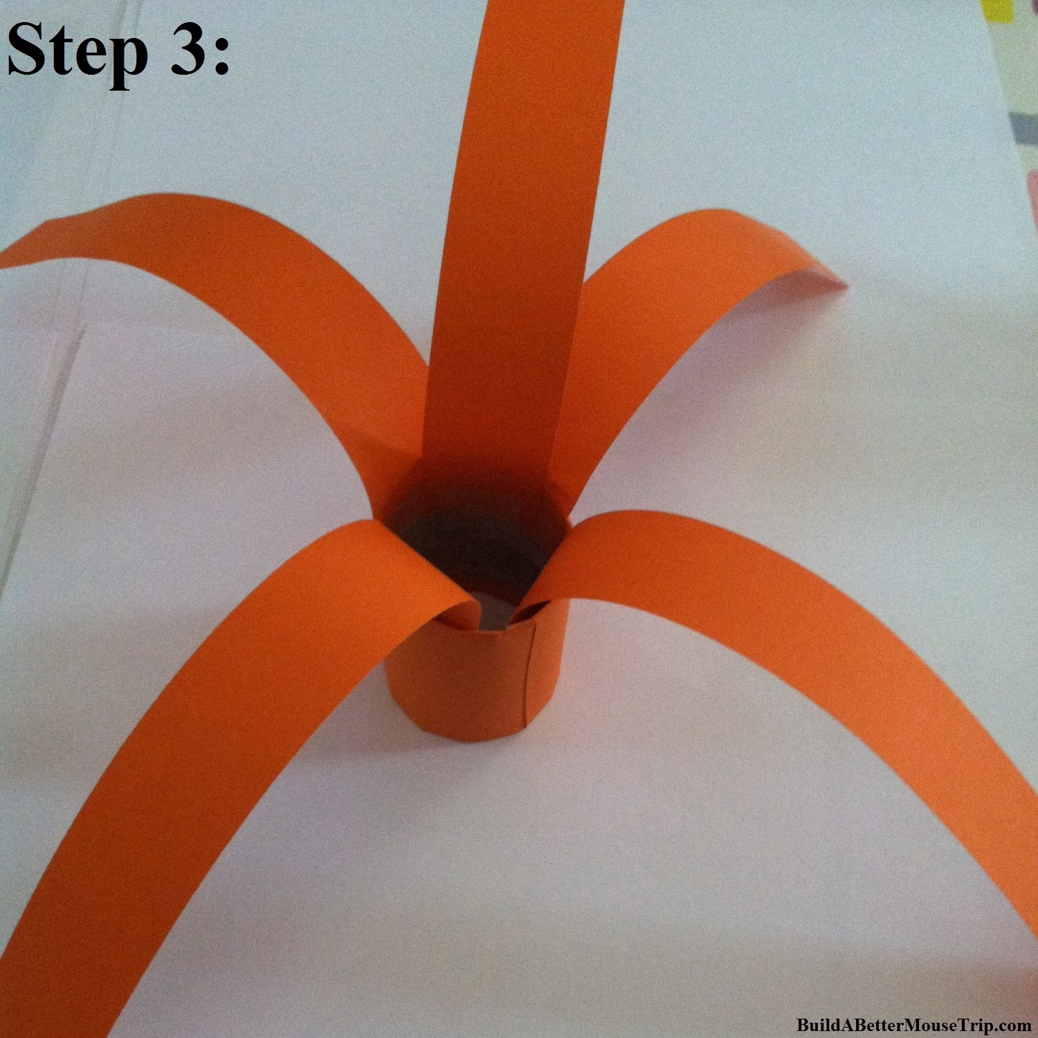 Orange construction paper strips form the body of your Mickey Mouse pumpkin.