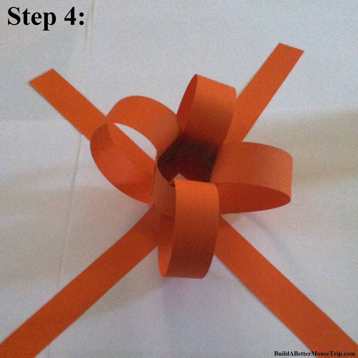 Step 4 - Attach one end of an orange construction paper strip to the inside of the bottom of the center tube and the other end to the top, using scotch tape or a glue gun.