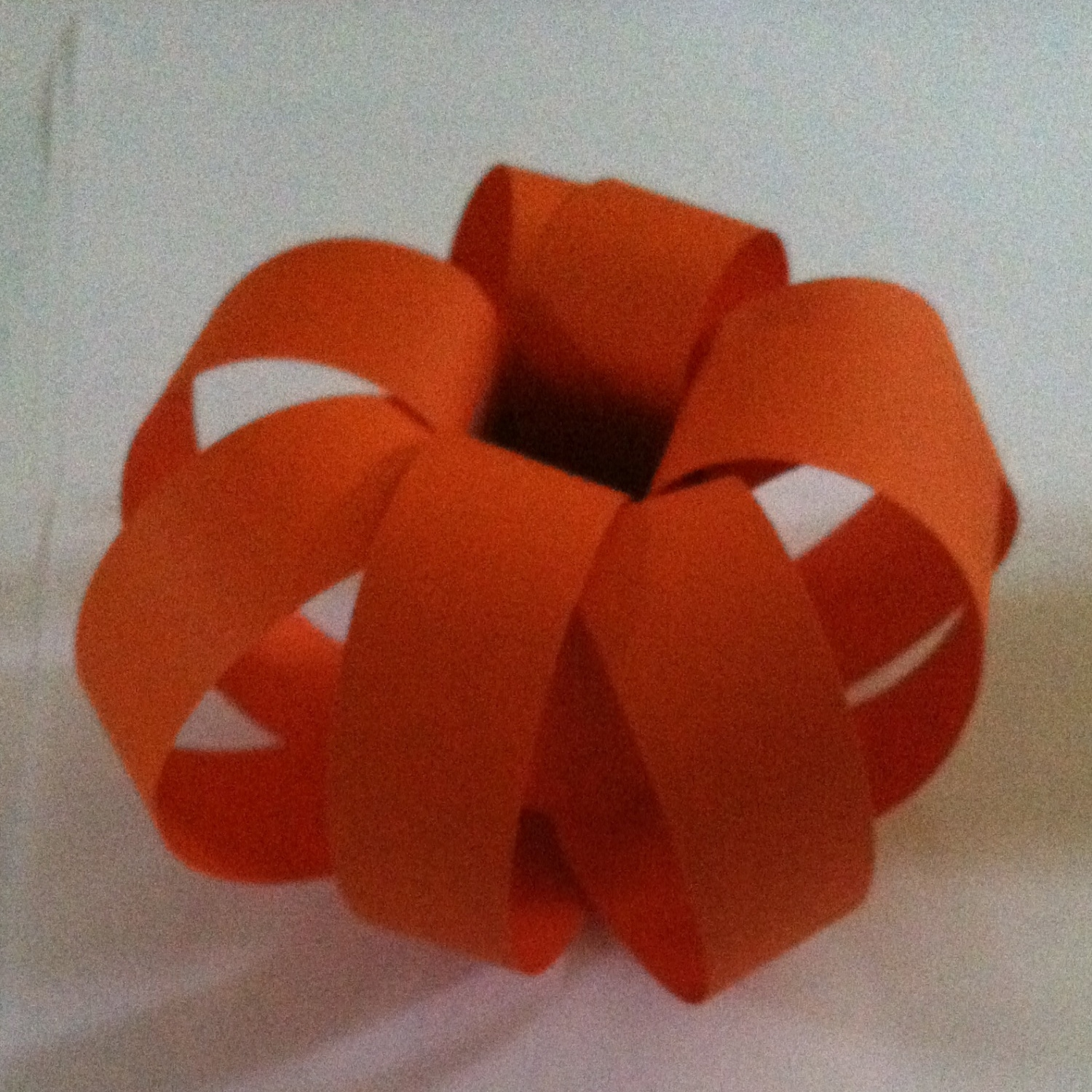 Step 4: Bring all of the orange construction paper strips down from the top of your pumpkin to the bottom and attach, making a nice round pumpkin shape.