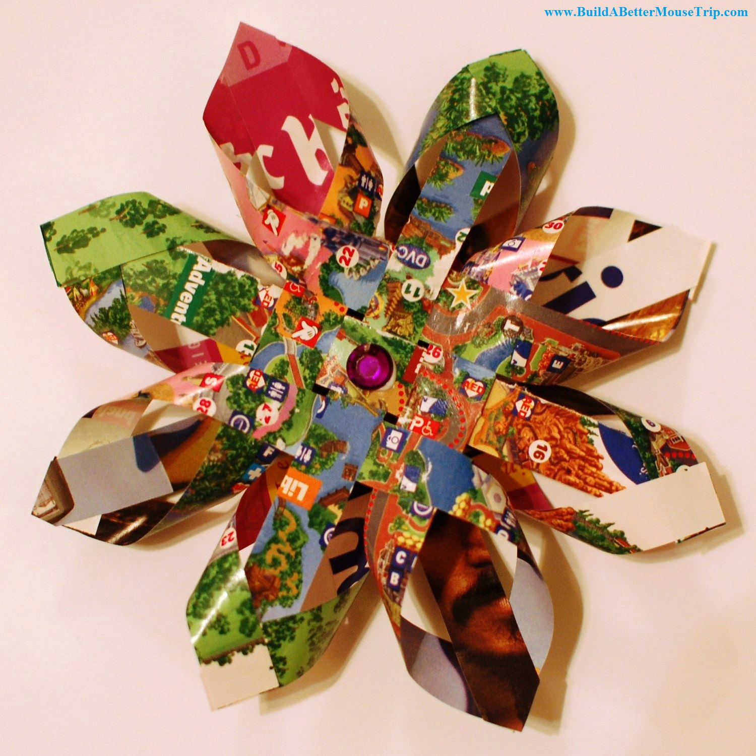 Snowflake ornament made from a Disney World park map - includes video instructions.  Easy craft project. See: http://www.buildabettermousetrip.com/disney-map-snowflake