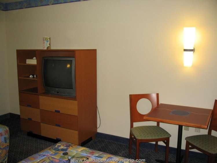 The rooms at Disney's Pop Century Resort have a dresser with TV and a small table with two chairs