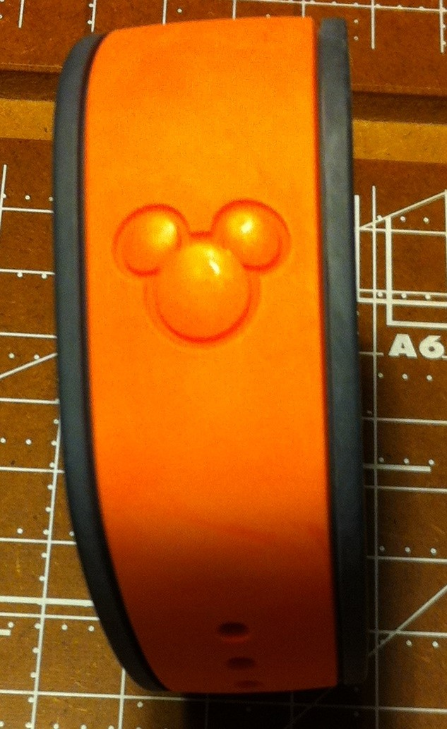 """A Comparison of the the """"New"""" and Old"""" Disney World Magic Bands - orange older style MagicBand."""