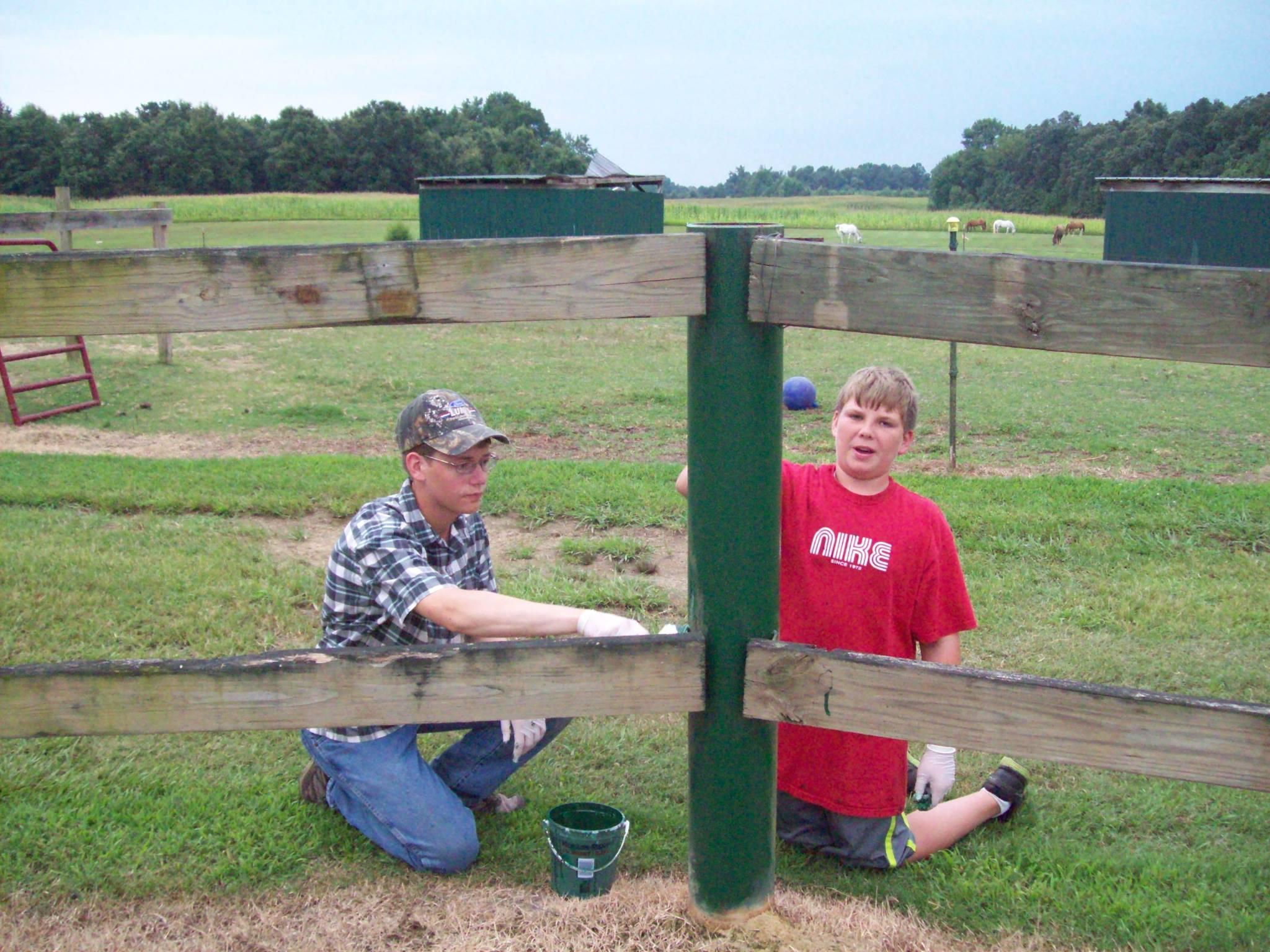Volunteers painting a fence at Mephibosheth Farms Angelic Riders