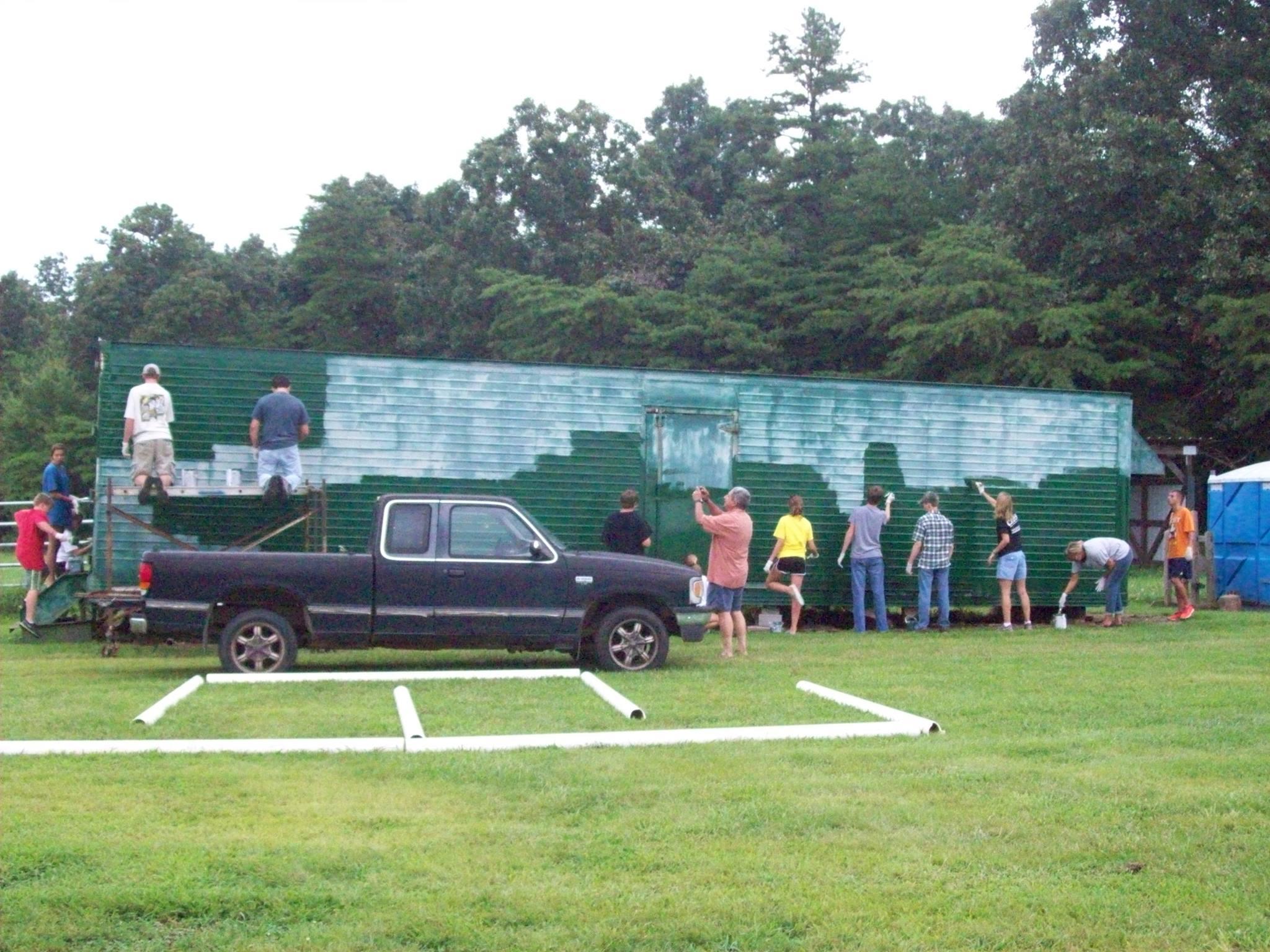 Group of vo  lunteers p  ainting the hay trailer  at Mephibosheth Farms Angelic Riders