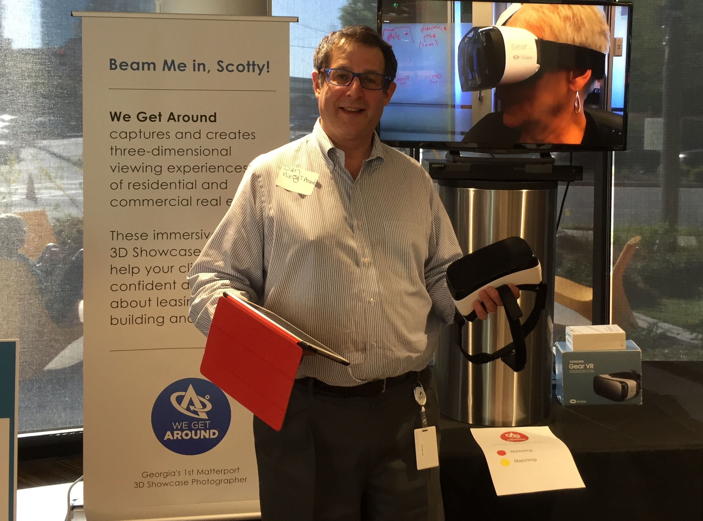 """We Get Around Founder, CEO and Chief Photographer Dan Smigrod at a Matterport Spaces (3D, VR) demo event. The shopping list below, includes the following items above: (left to right): Retractable banner; iPad Air 2, Gear VR, Samsung Galaxy 7 smartphone; Insignia 48"""" TV; Samsung Blu-ray TV; pedestal; HDMI cable. Other items not pictured: DVD burner; recordable DVDs; extension cord; power strip; duct tape; alcohol sterilizing pads and luggage cart."""