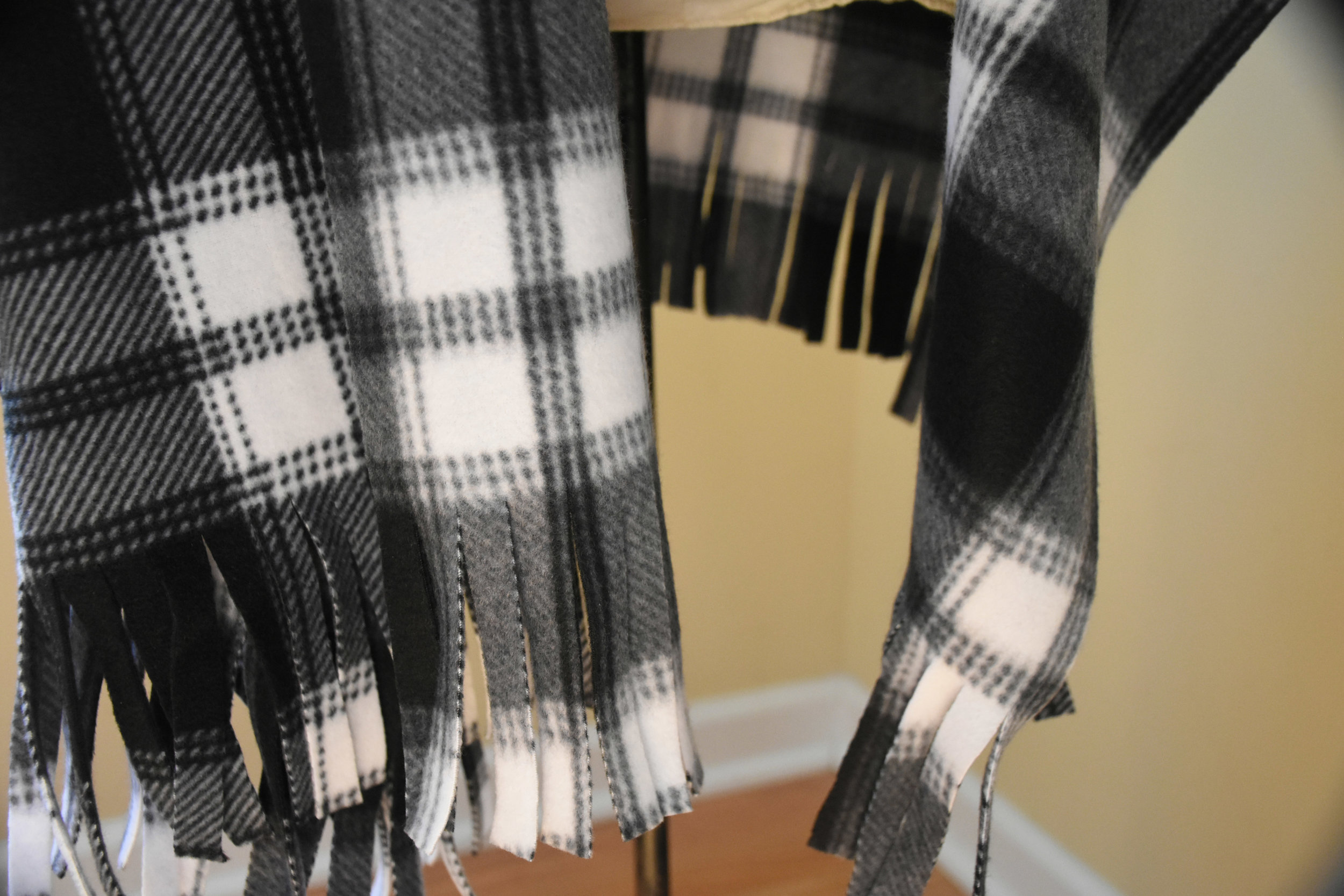 This is cut fringe in craft fleece. If you have a woven wool fabric, you can pull the threads to create fringe.