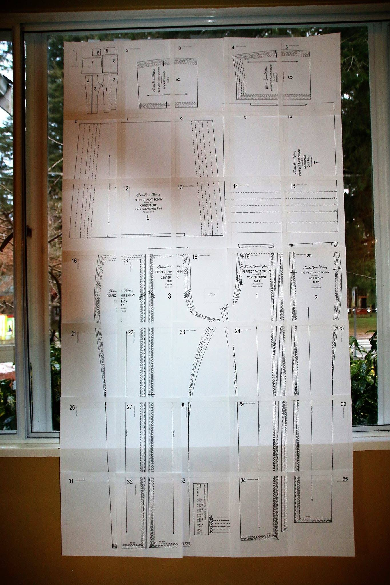 Downloadable sewing patterns like the Perfect Pants, shown here, can easily be printed, matched and taped up even if your printer cuts off one of the borders. Putting it up on your window or glass door like this is an easy way to see how the pattern lines up as you tape.