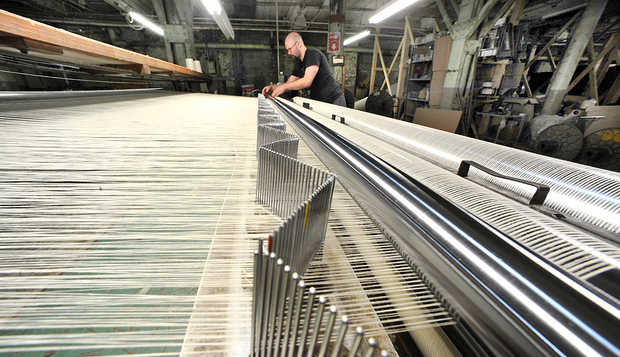 Rene Cote looks for a break in the line on the slasher machine at Maine Heritage Weavers in Lewiston. |  RUSS DILLINGHAM/SUN JOURNAL