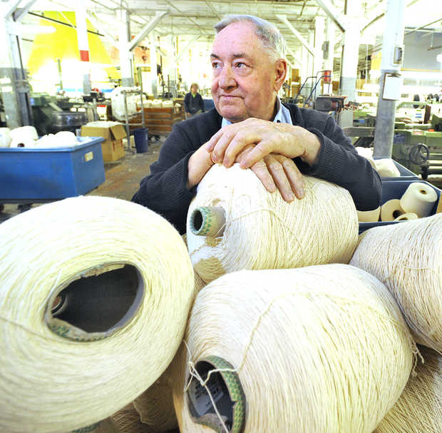 Fred Lebel looks out at the looms running at Maine Heritage Weavers in Lewiston, which he and his daughter Linda own. |   RUSS DILLINGHAM/SUN JOURNAL
