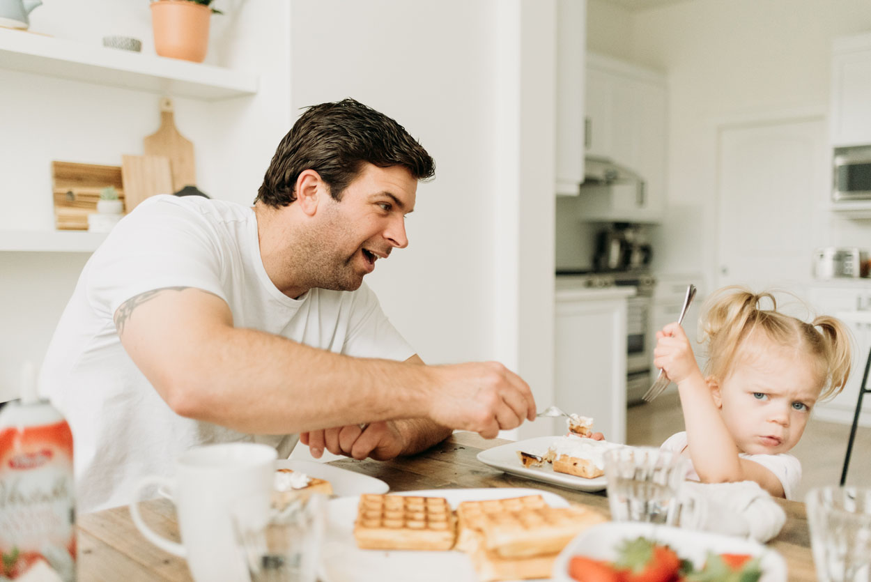 Dad trying to feed his daughter waffles