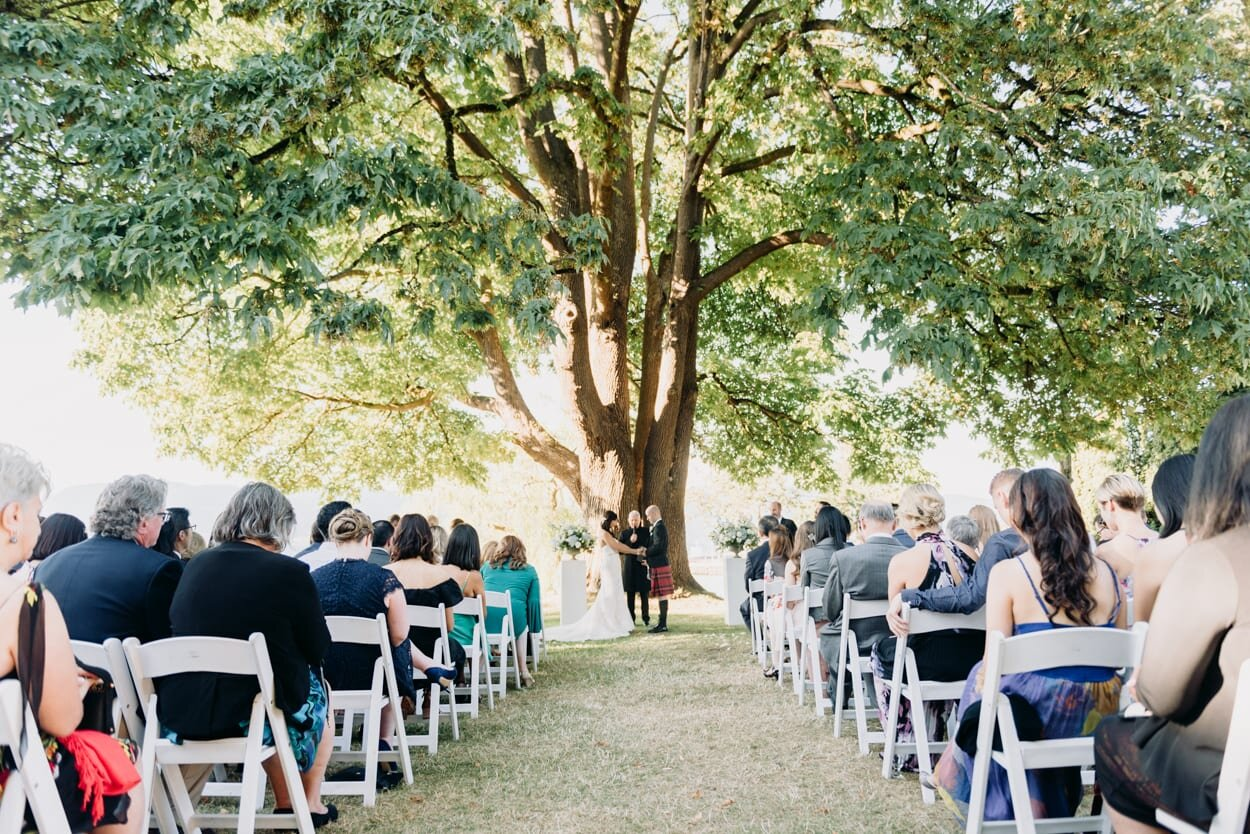 Bride and groom standing at end of aisle under a tree