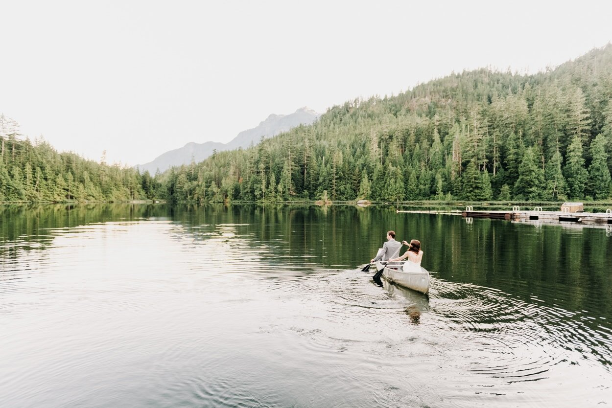 Bride and groom rowing canoe on lake surrounded by trees